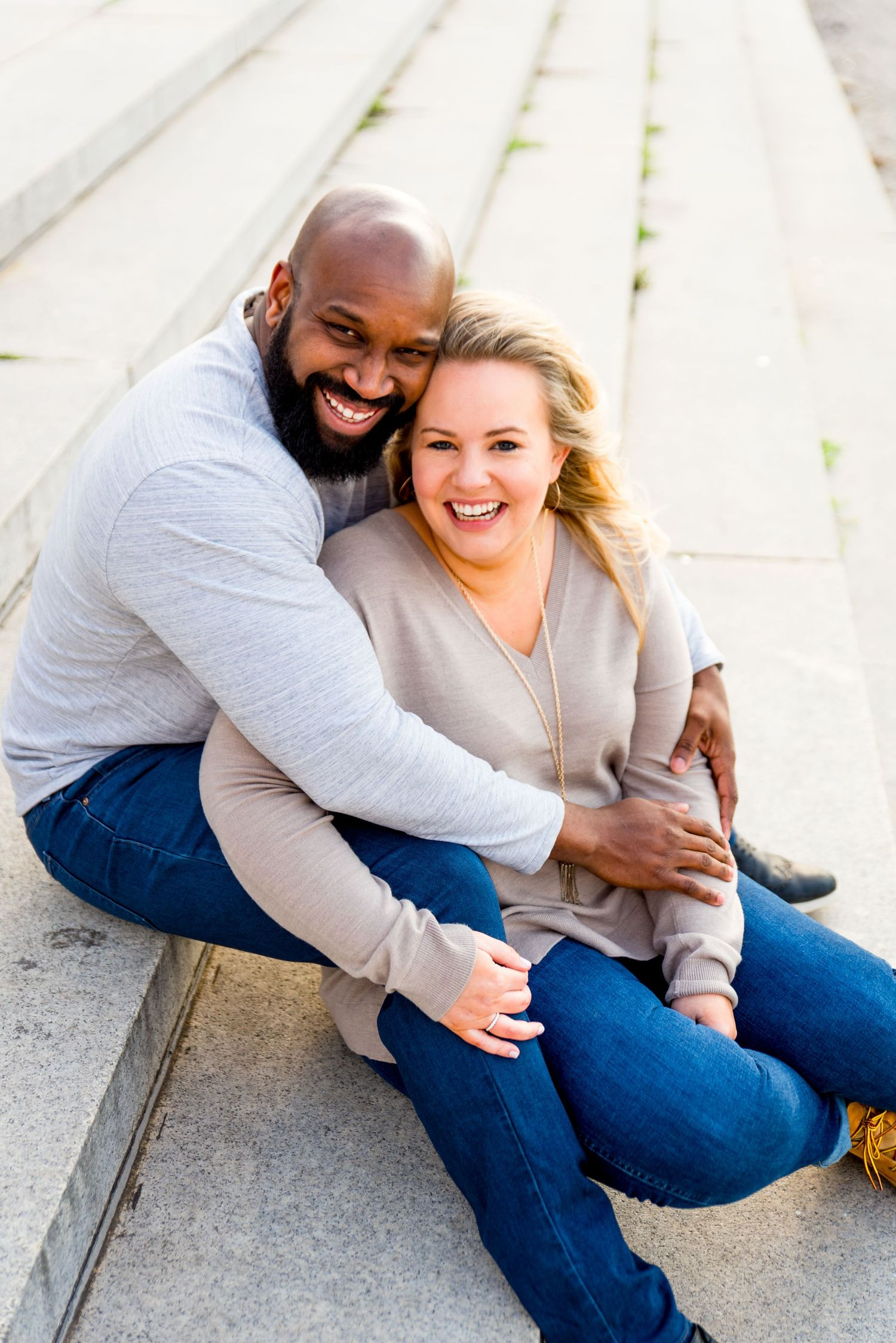 man and woman sitting on stairs in Grant Park laughing during Chicago sunrise engagement photos