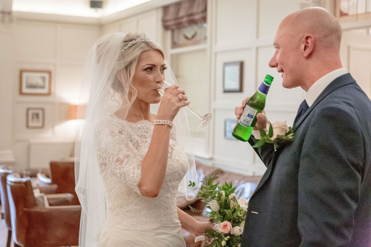 bride and groom enjoying a quick drink together before greeting their wedding guests