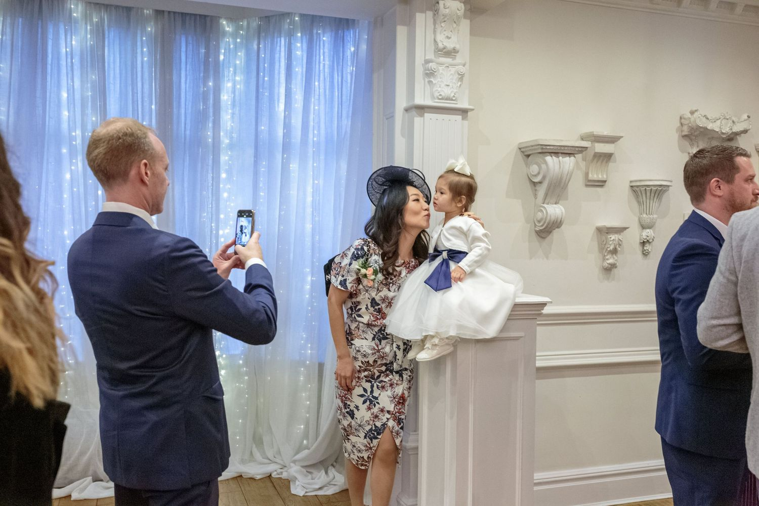 brides brother takes a photo of his wife and young daughter sitting on a pillar in the ceremony room at ashfield house