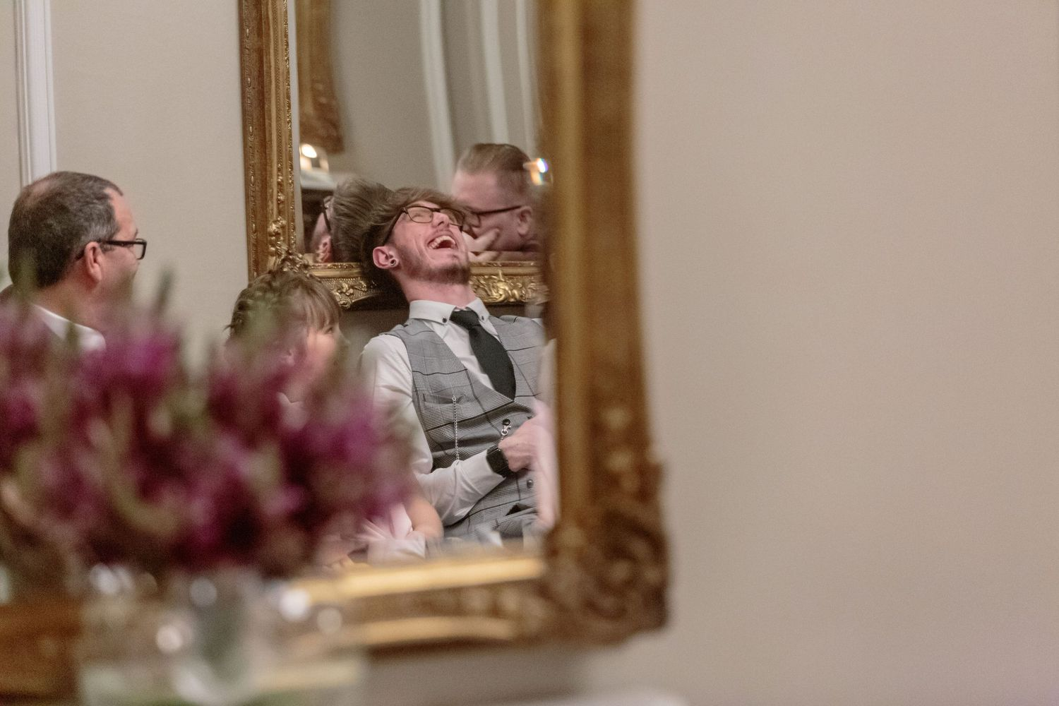reflection shot in an ornate mirror of wedding guests laughing and chatting