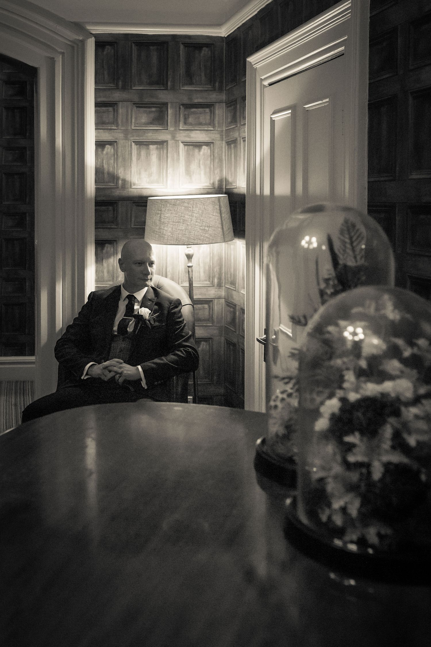 atmospheric black and white shot of the groom sitting at the end of a desk indoor a floor lamp