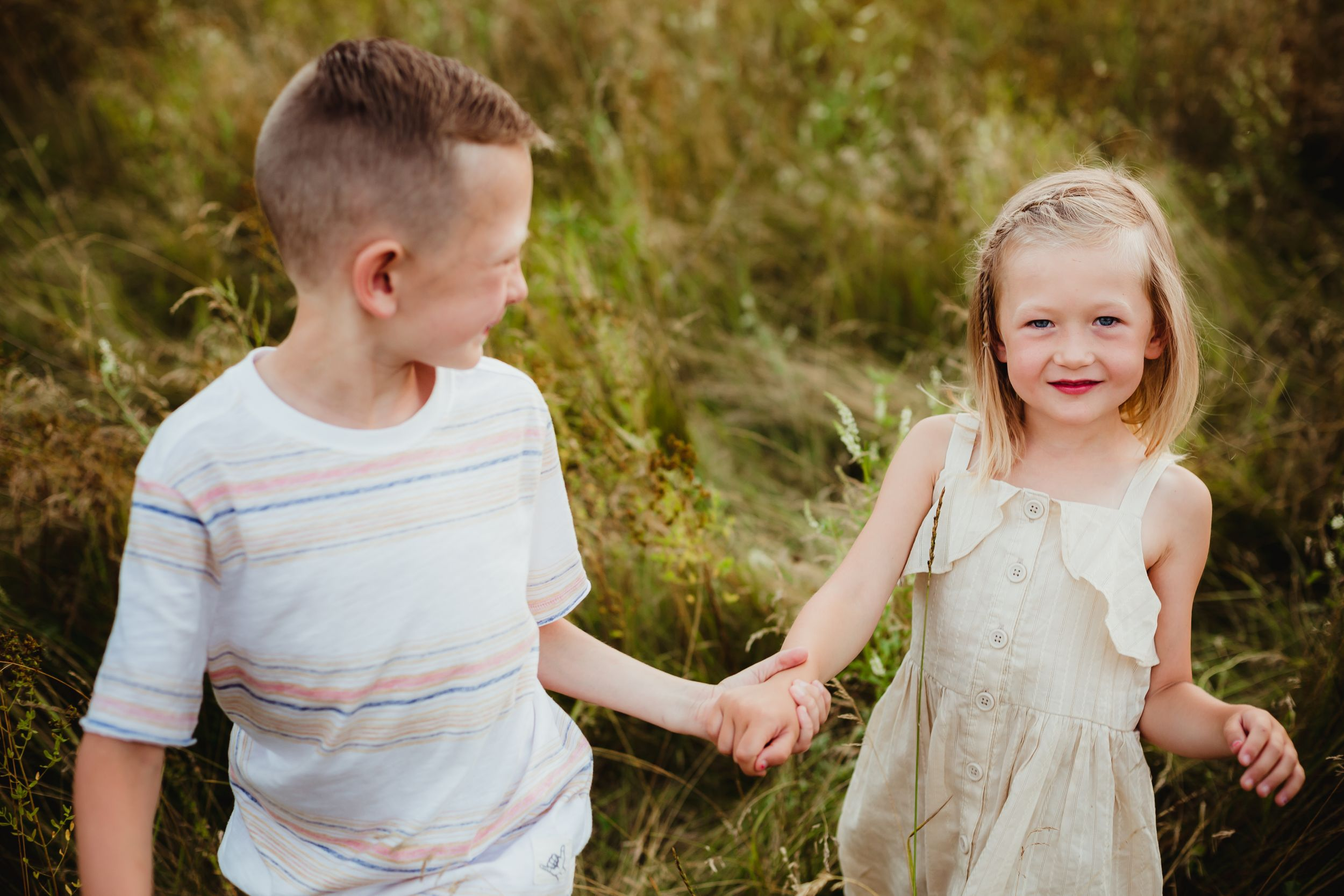 A young brother and sister holding hands walking through a field. He smiles at her and she smiles at the camera.