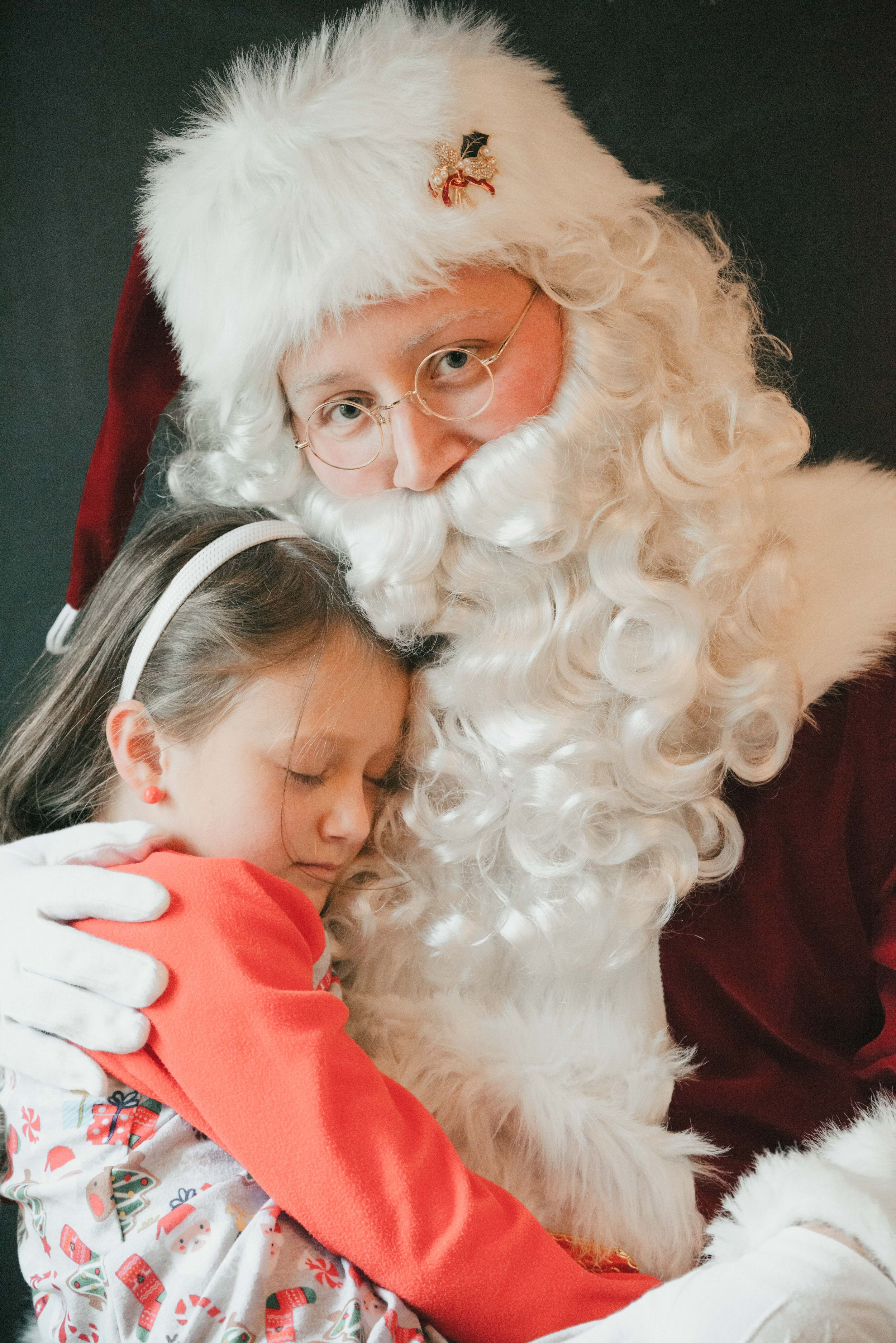 Santa with sleeping child in Christmas pajamas, Shiny Penny Studios, Cleveland