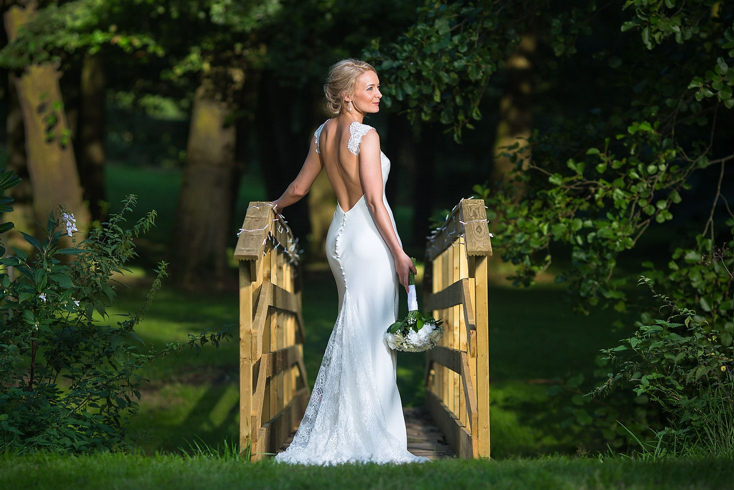 Beautiful blonde haired bride standing on a wooden bridge outdoors holding a bouquet of flowers wearing a white wedding