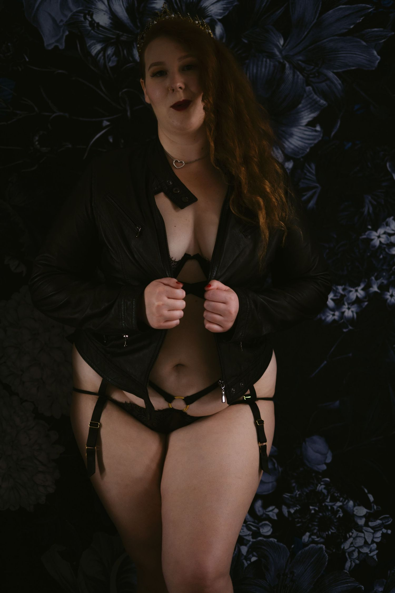 A woman in a black leather jacket and black lingerie