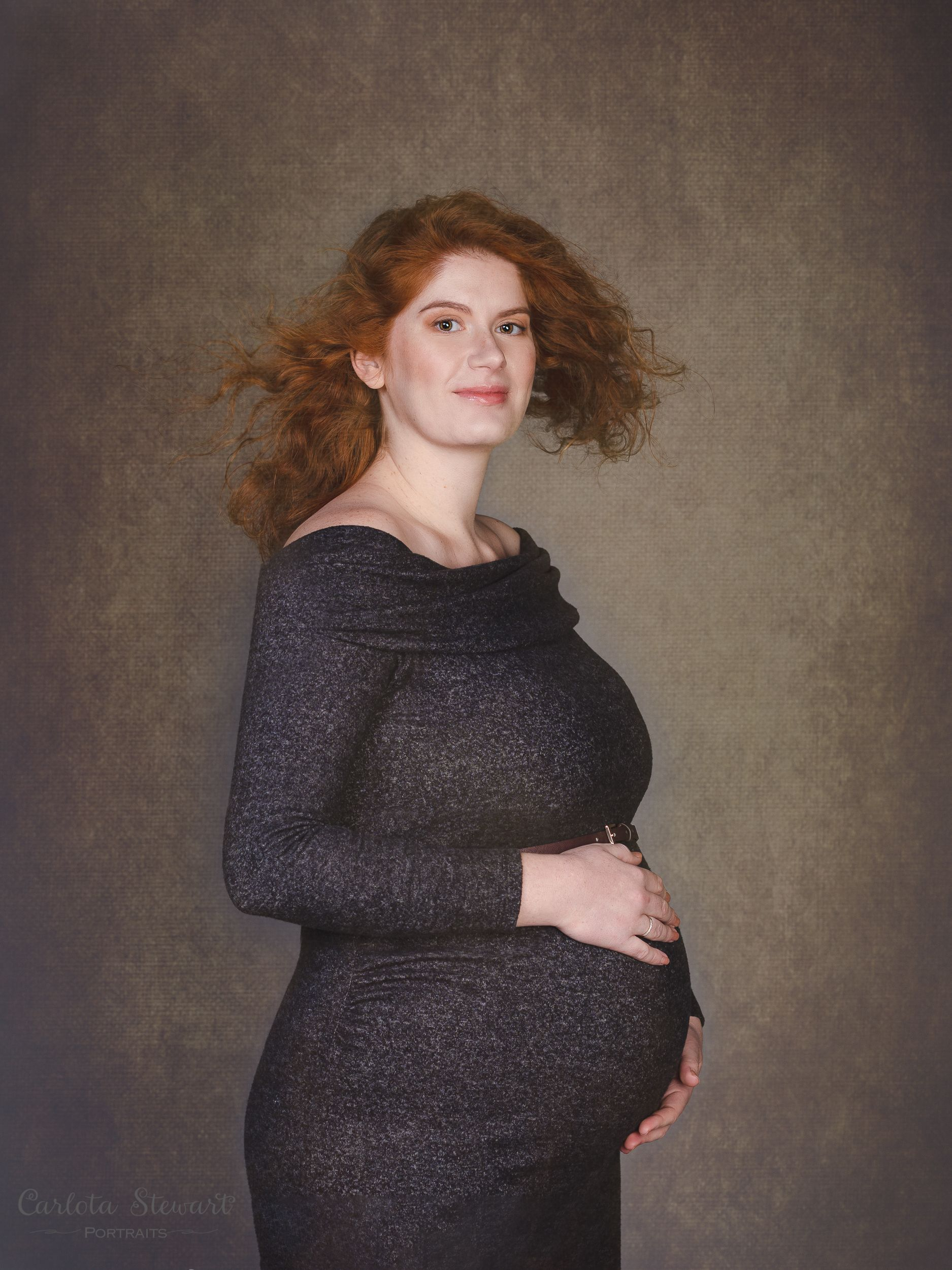 Photo of expectant mother wearing a grey dress looking at the camera.