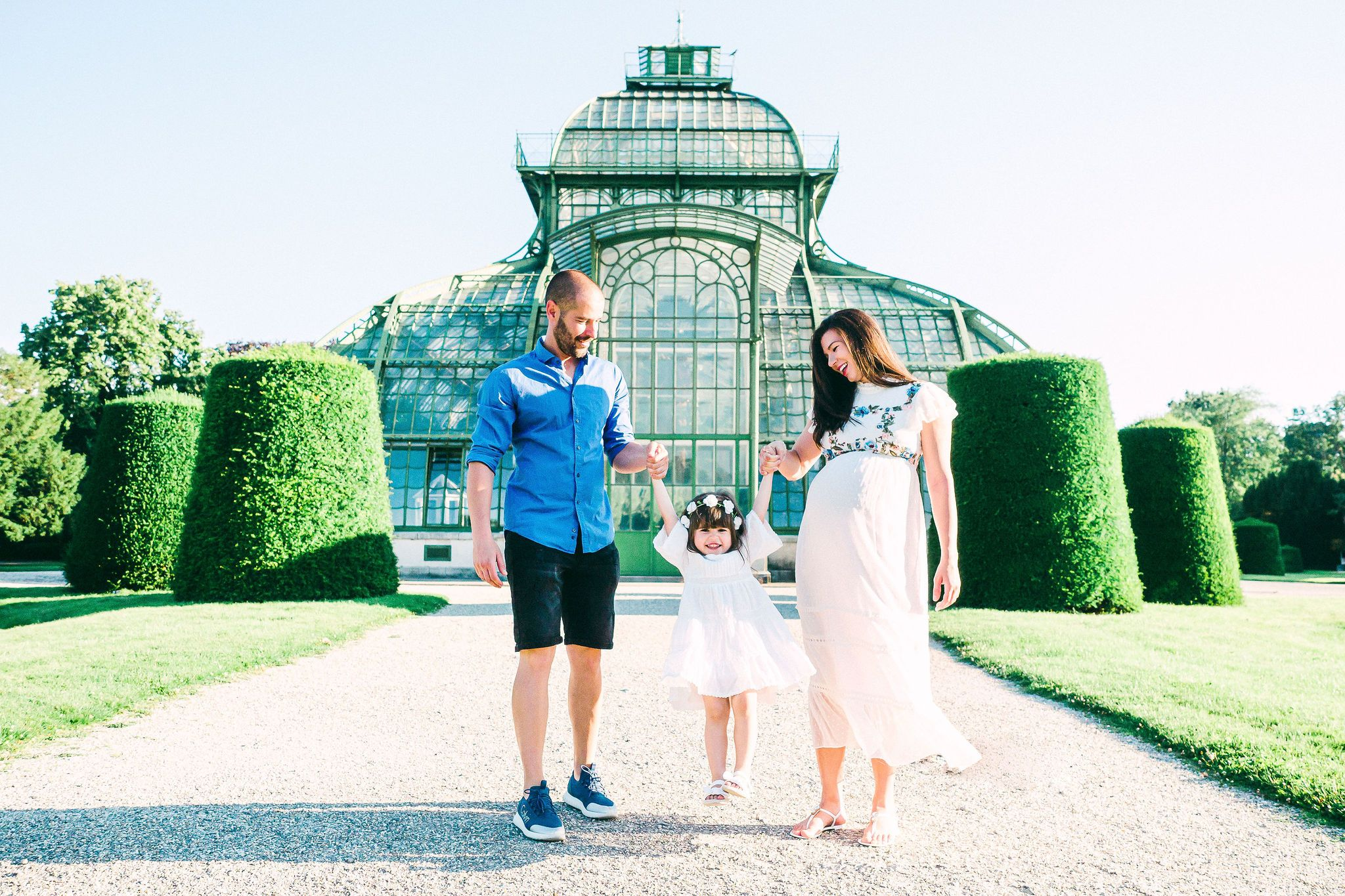 Pregnant mother and father swinging their dauther in a bright sunny day at the Schönbrunn Palmenhaus in Vienna
