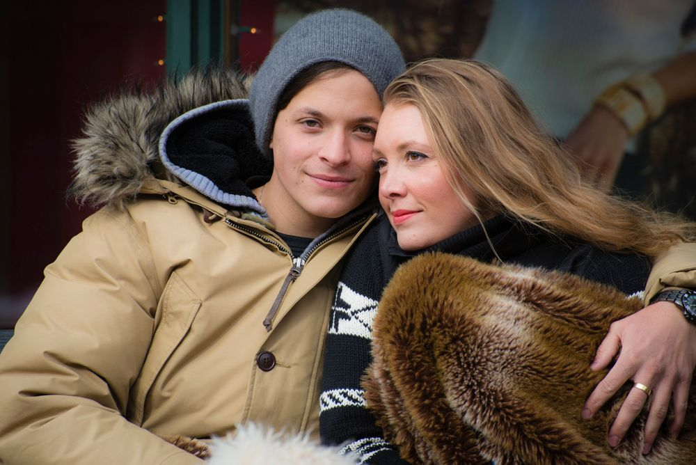 Couple in winter clothing and fur blanket on a bench in Vail Village in winter