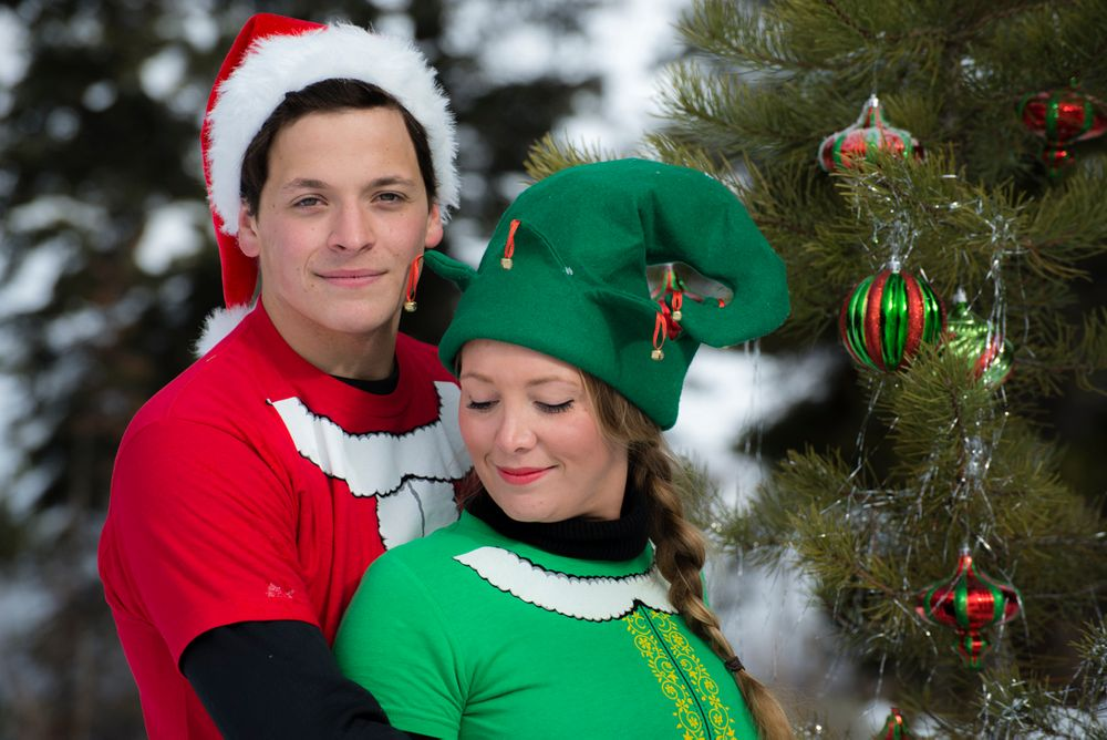 Sexy photo outside in front of fur tree with decorations and couple dressed as Santa's helpers, in winter
