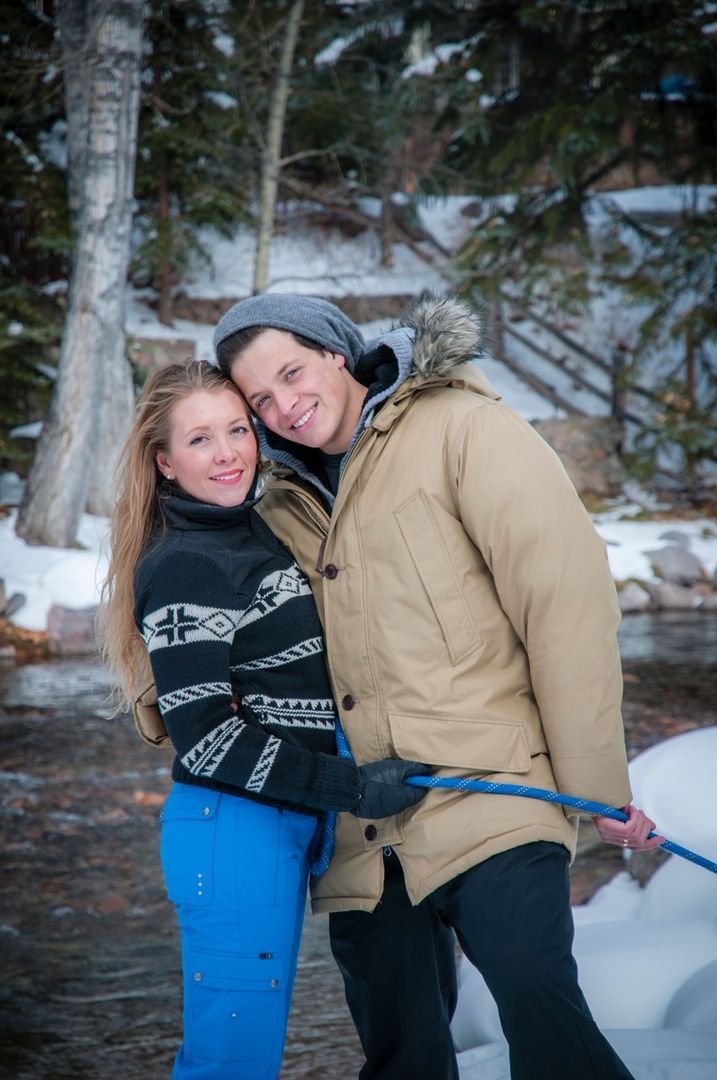 Couple in front of creek in Vail in winter