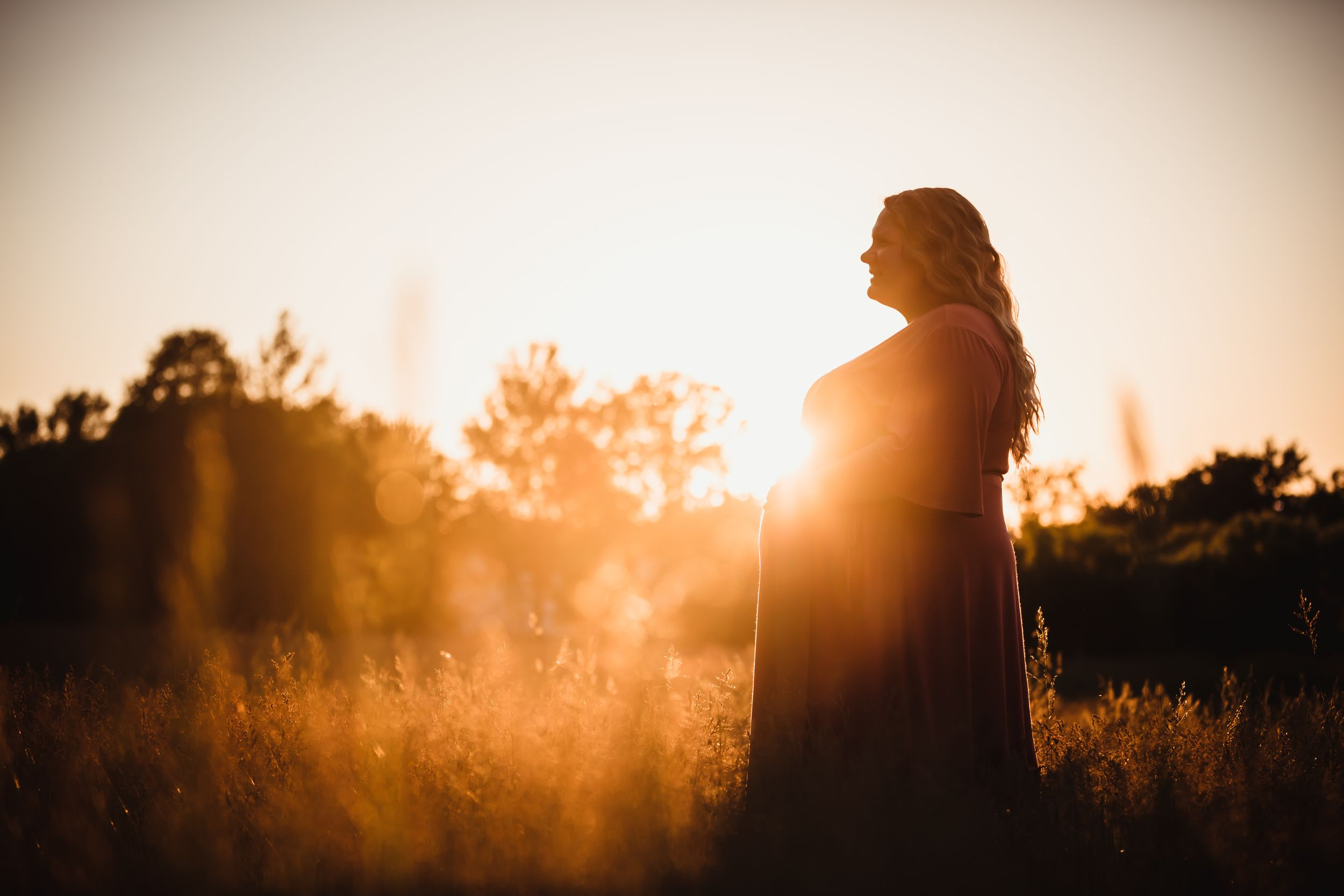 Pregnant mom in a long dress standing in a field with golden sunset light.