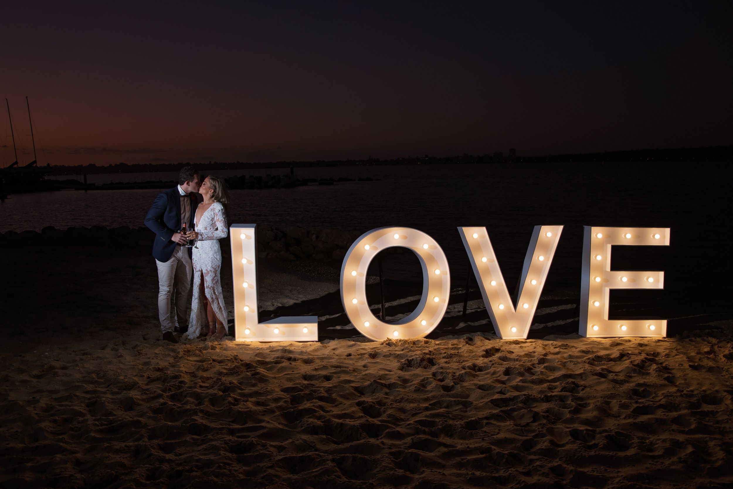 bride and groom at night kissing next to love letters