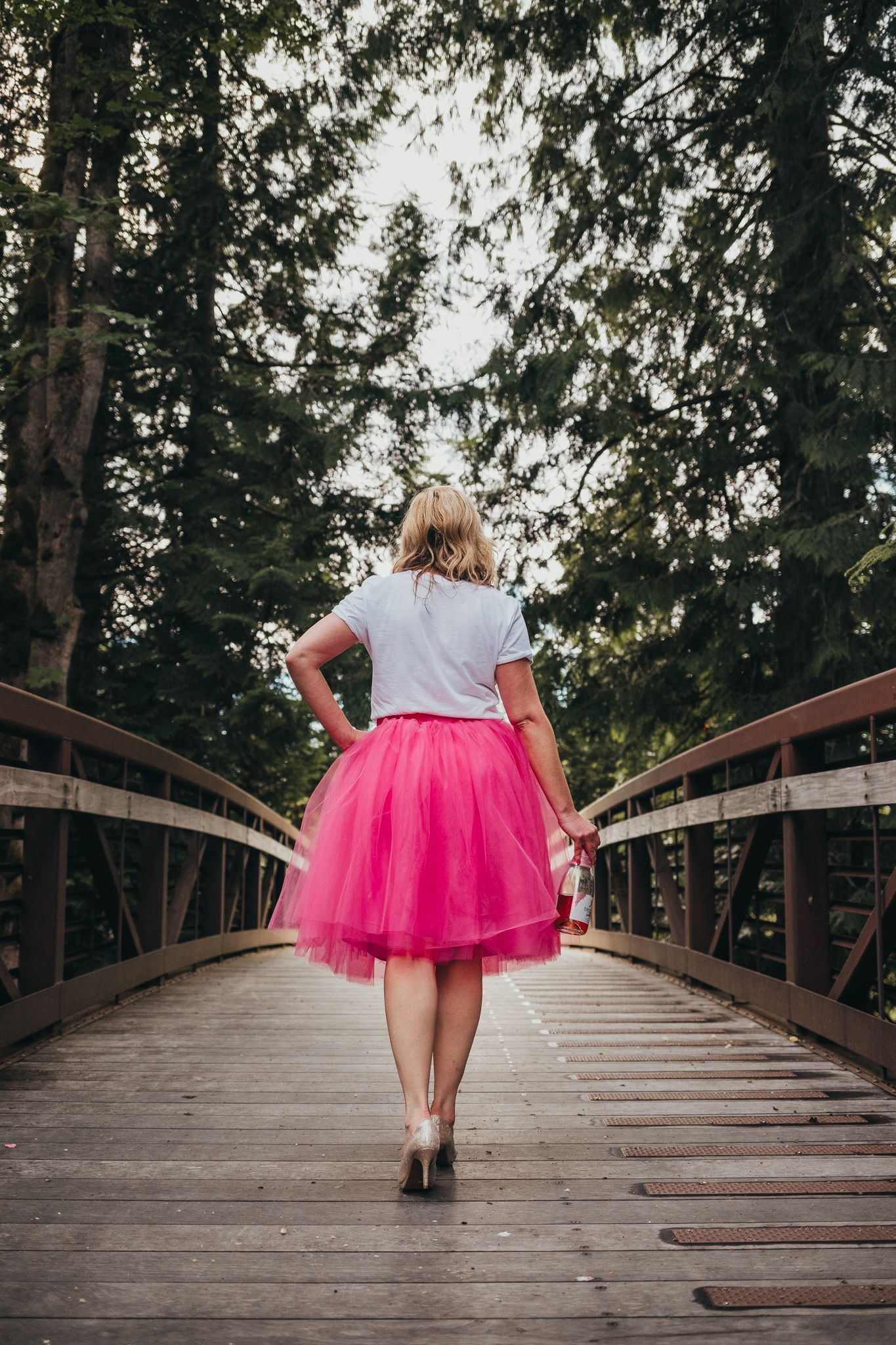 woman holding champagne walking down dahlia park bridge