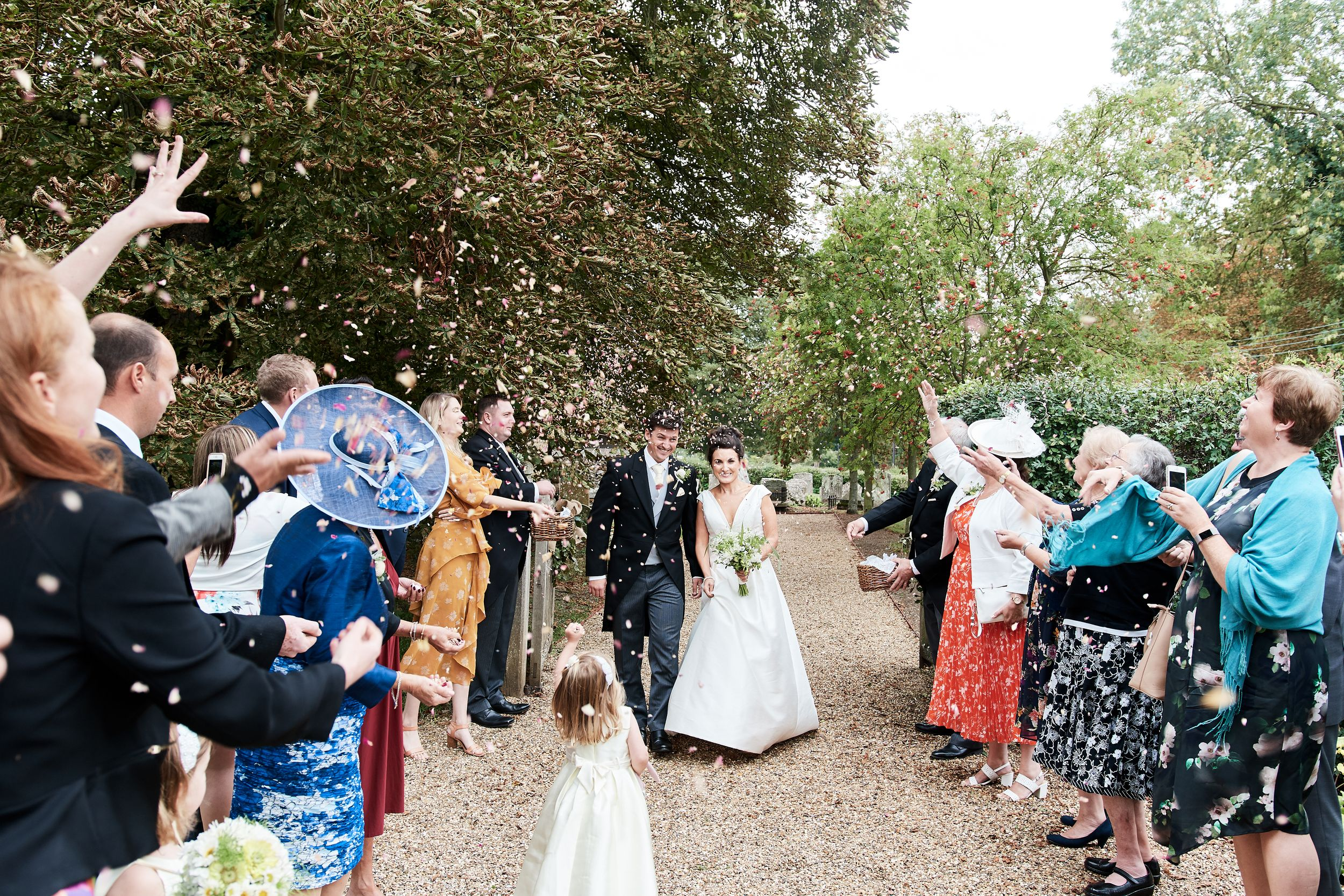 wedding guests throw confetti over the bride and groom at The Garden Barn in Suffolk. by Suffolk wedding photographer