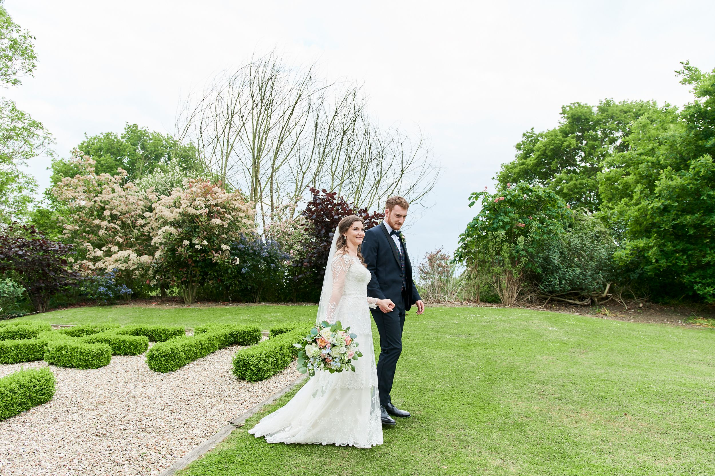 Bride and groom walks through the gardens at Orsett Hall, Essex. by Essex wedding photographer