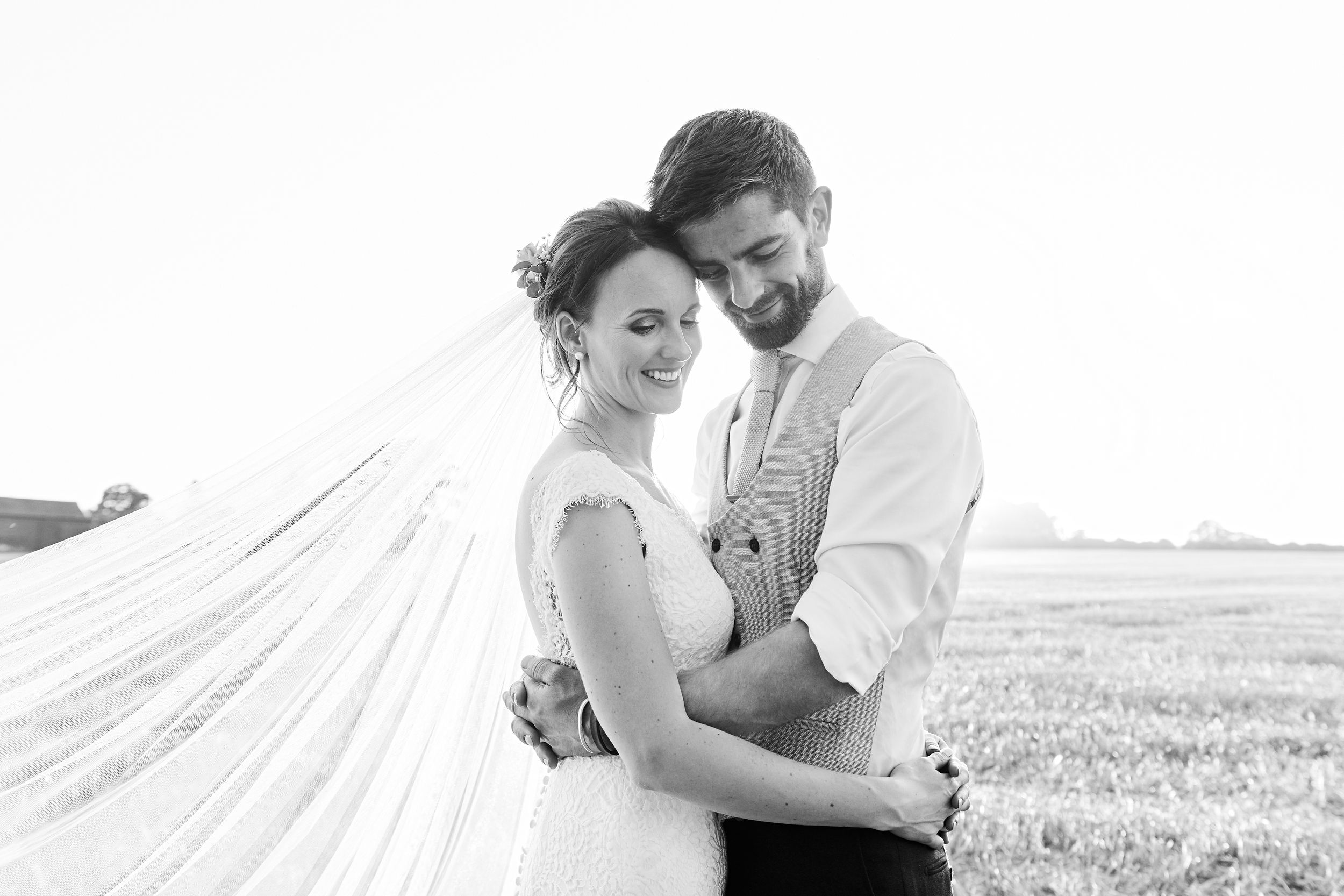 bride and groom share a hug at sunset at their farm wedding in Norfolk. by Norfolk wedding photographer