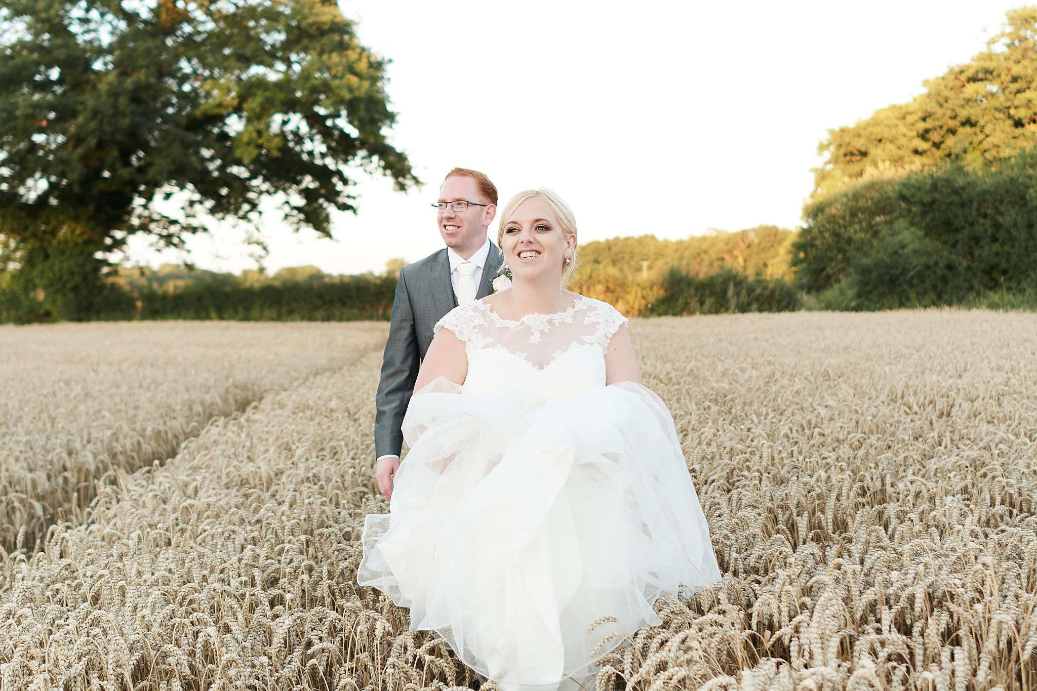 bride and groom walk through a field at sunset on their wedding day at the Boathouse, Norfolk. by Norfolk photographer