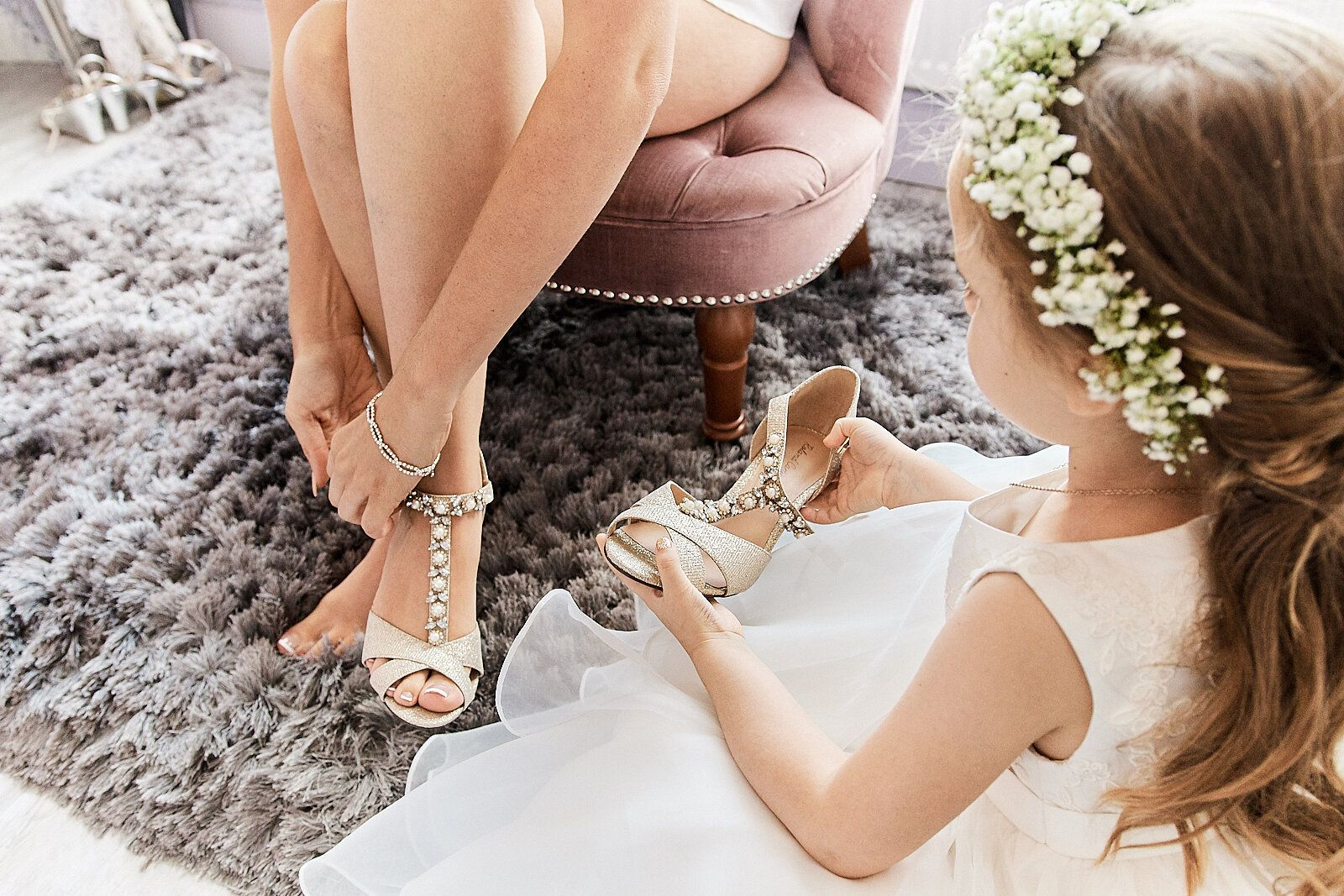 flower girl holds bride's shoe as she puts them on, at The Stables, Kings Lynn. by Norfolk wedding photographer