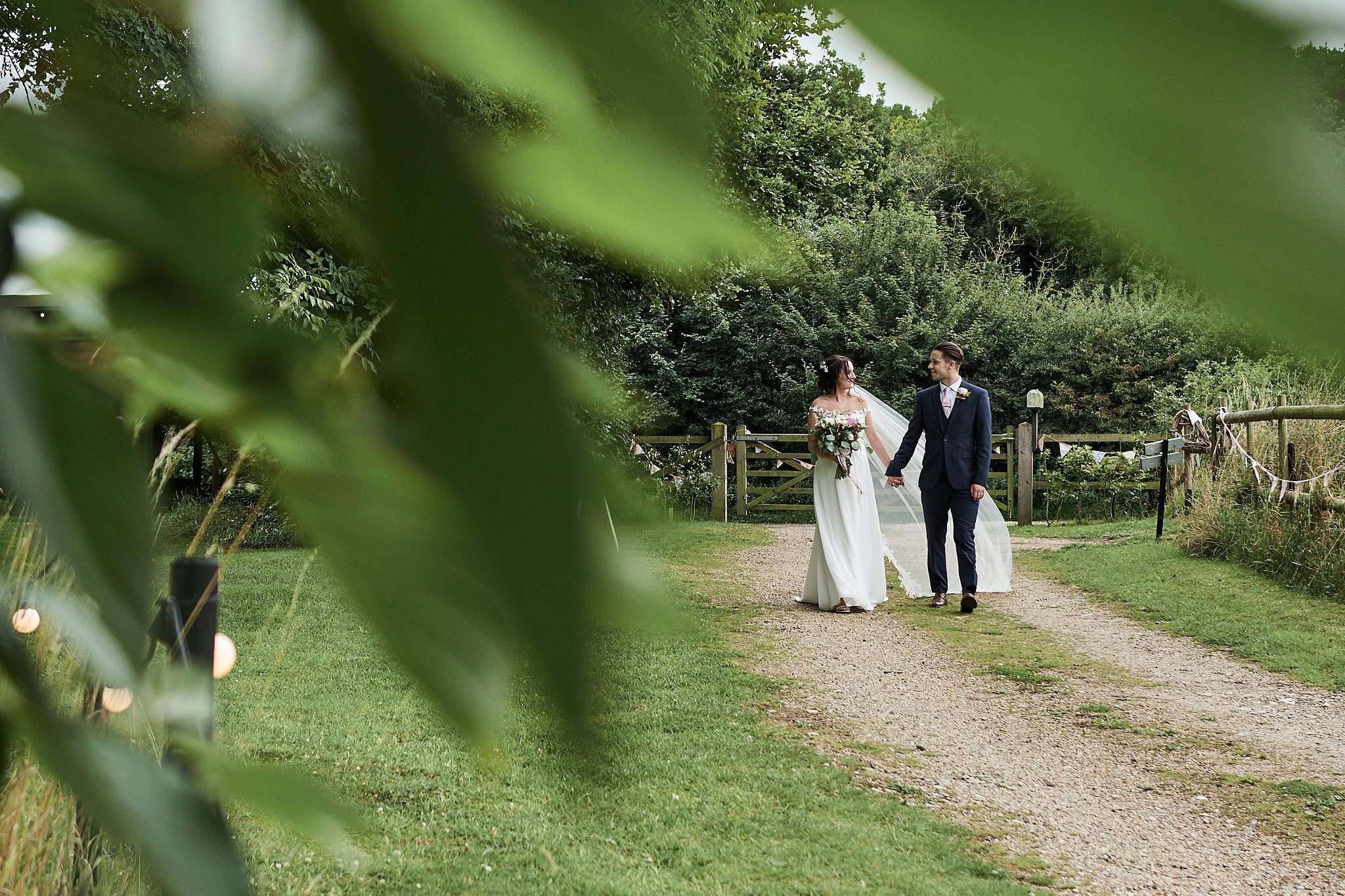bride and groom walk through the grounds at The Keeper and the Dell, Norfolk. by Norfolk wedding photographer