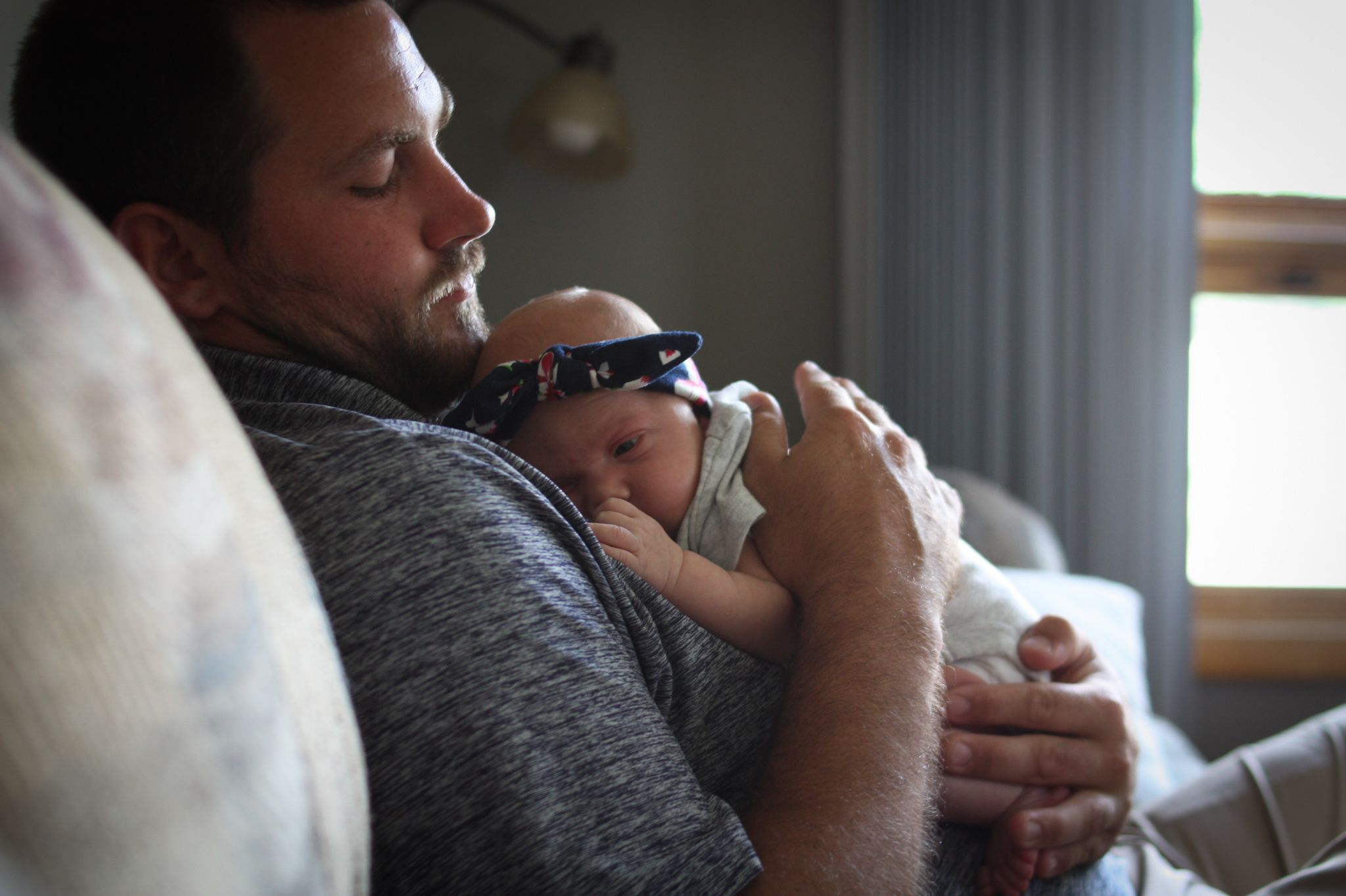 Baby girl snuggling her dad during her in-home newborn session in Sioux City, IA.