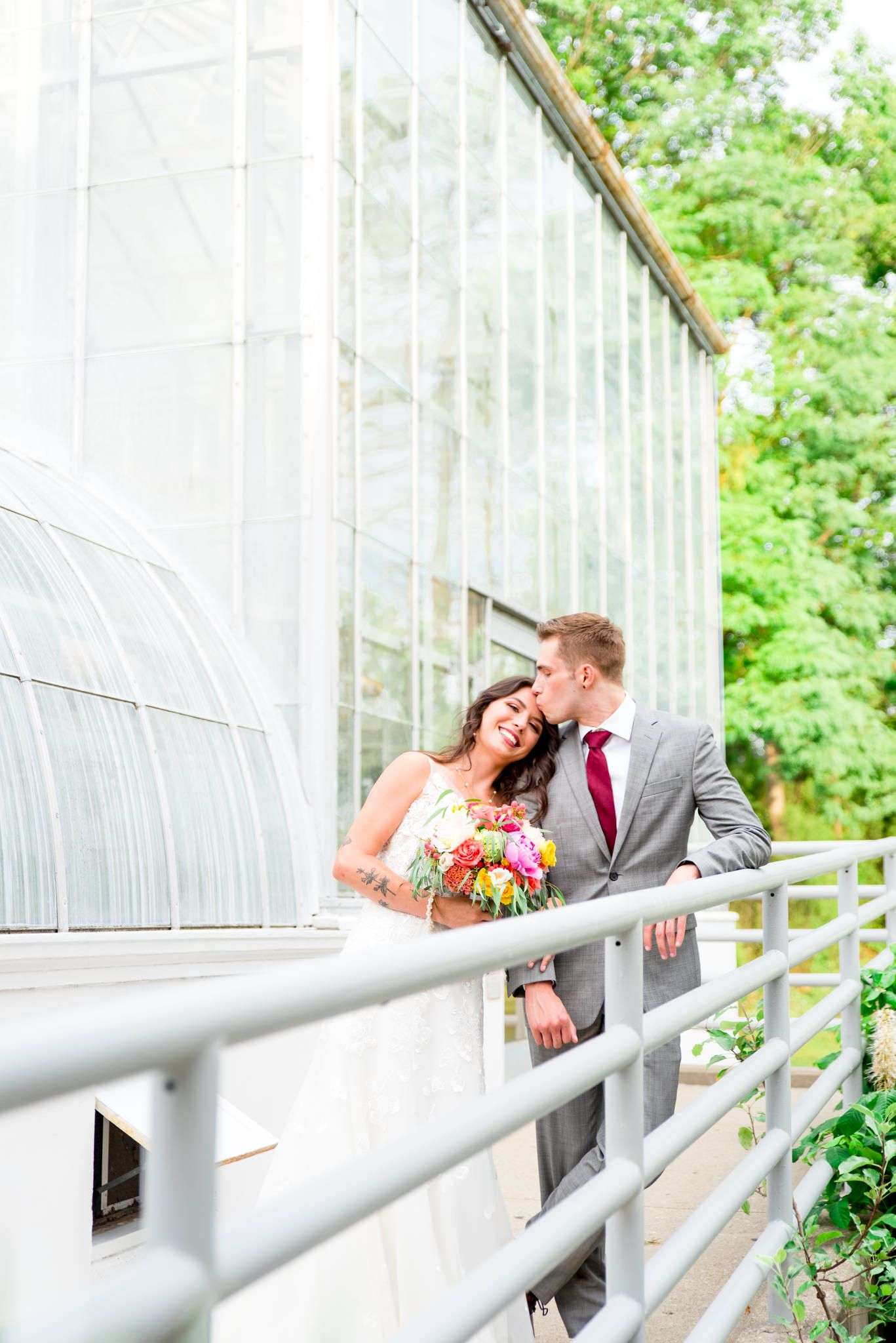 groom kissing bride on forehead at their Krohn Conservatory Wedding while bride smiles
