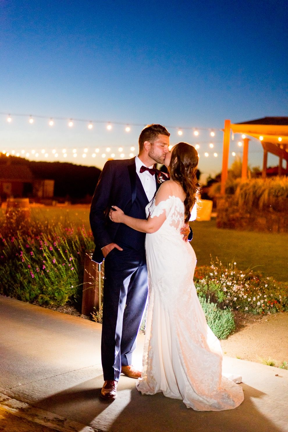 young married couple hugs and kisses under the blue night sky and string lights at Pennyroyal Farm wedding