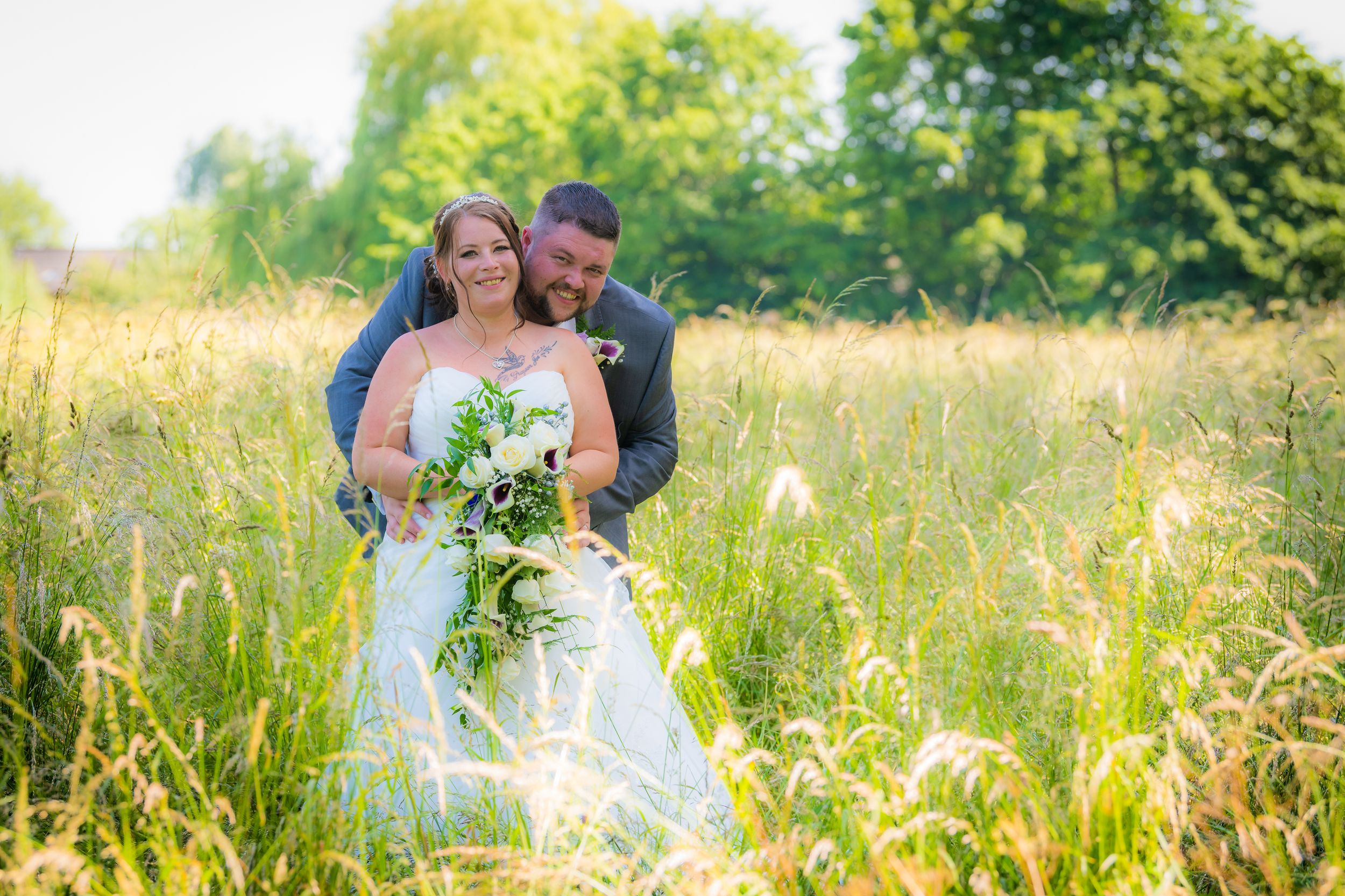 large groom behind his bride in then fields