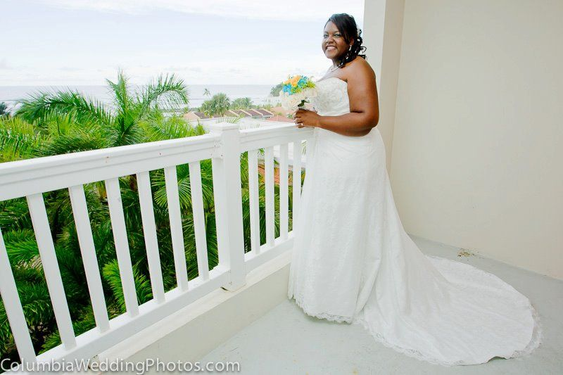 Bride poses for bridal portrait on the balcony of the Embassy Suites before a beach wedding in Dorado, Puerto Rico