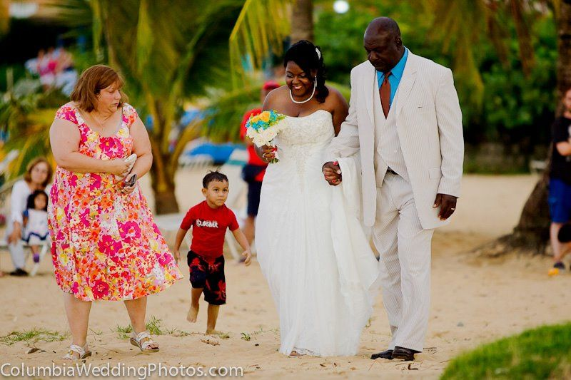 Father walks bride down the aisle during a beach wedding at Embassy Suites in Dorado, Puerto Rico