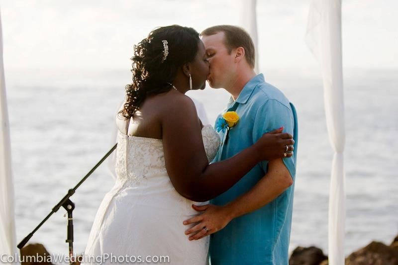 Bride and groom share their first kiss during a beach wedding at Embassy Suites in Dorado, Puerto Rico
