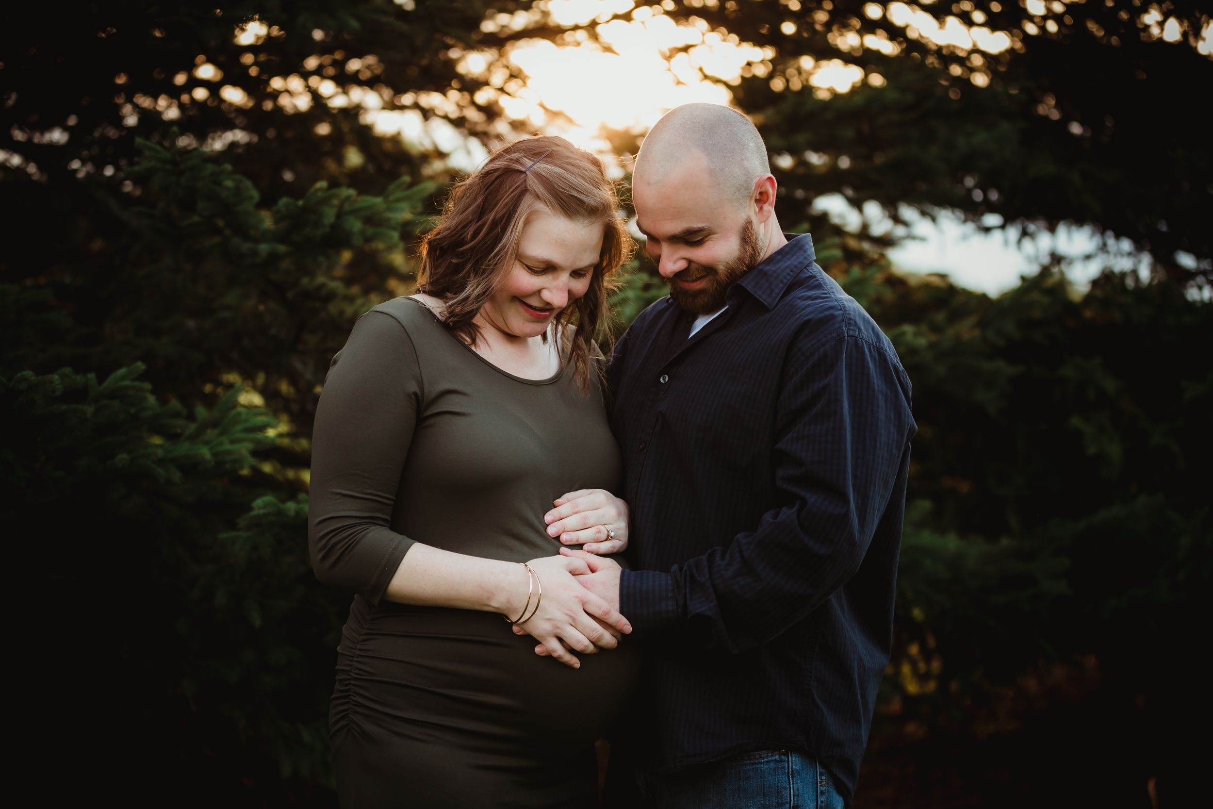 Pregnant woman and husband holding her belly, looking down at it, standing in front of pine trees.