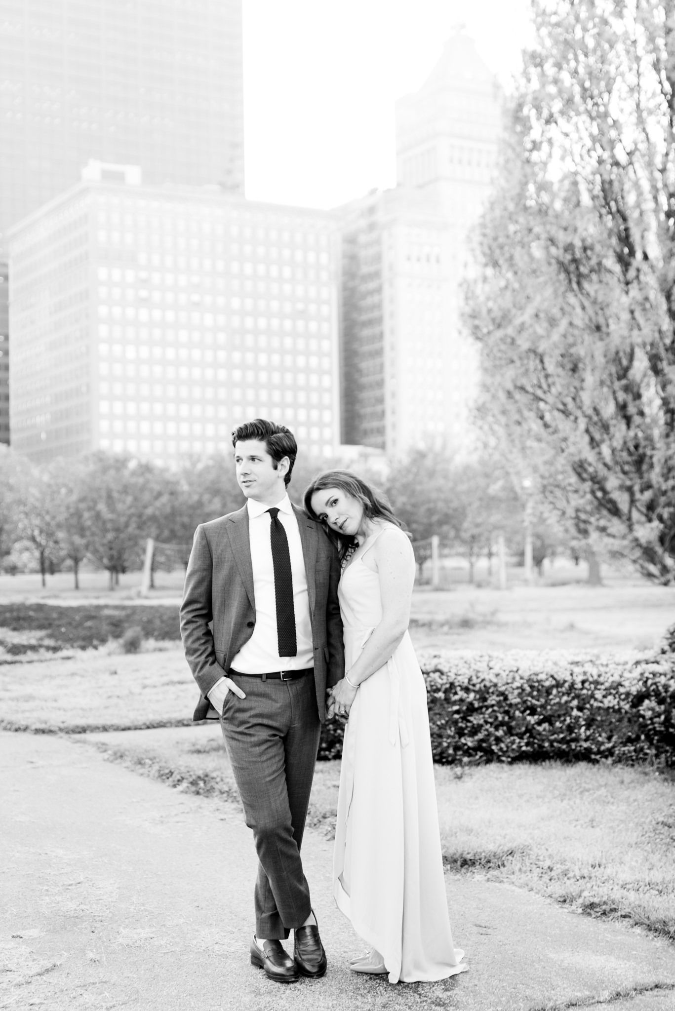black and white photo of man looking to side and fiancee leaning on his shoulder in Chicago Grant Park for engagement