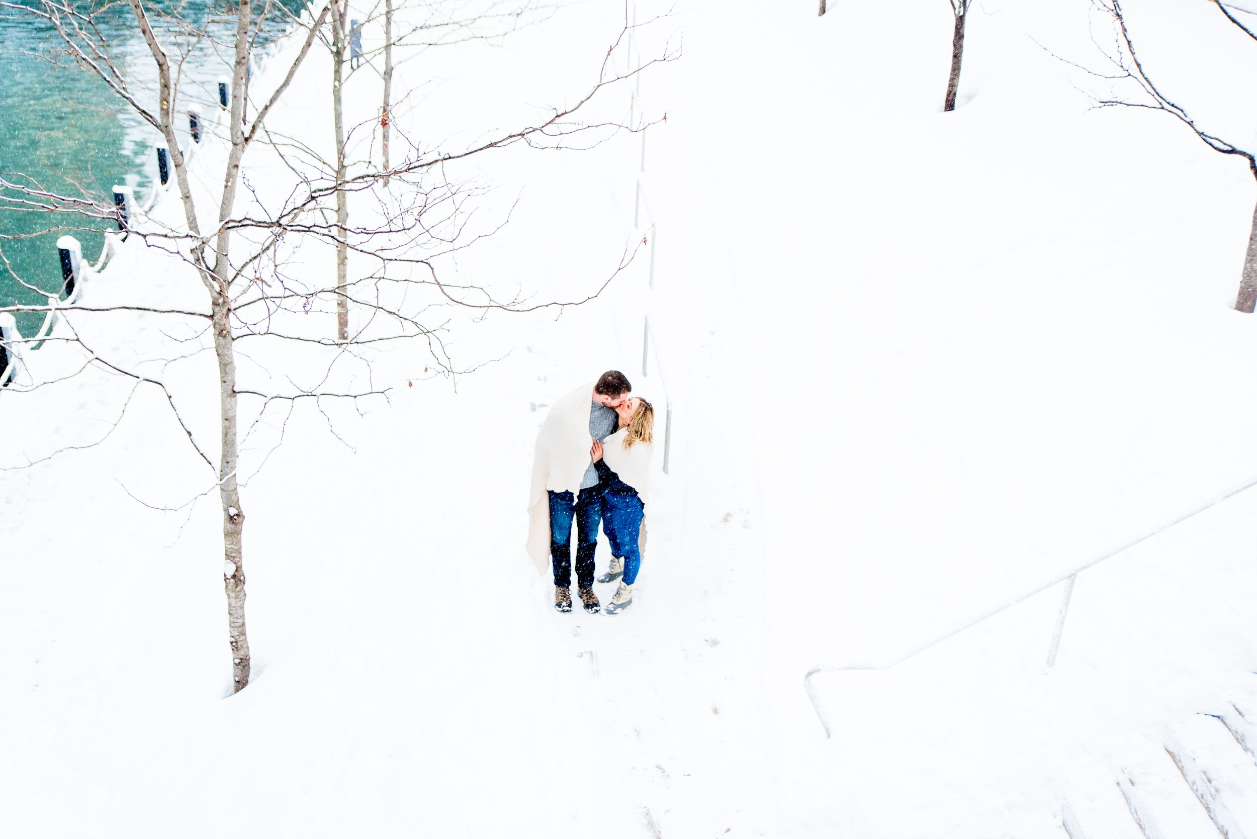 young engaged couple wrapped in blanket on the stairs at Chicago Riverwalk for snowy engagement pictures in Chicago