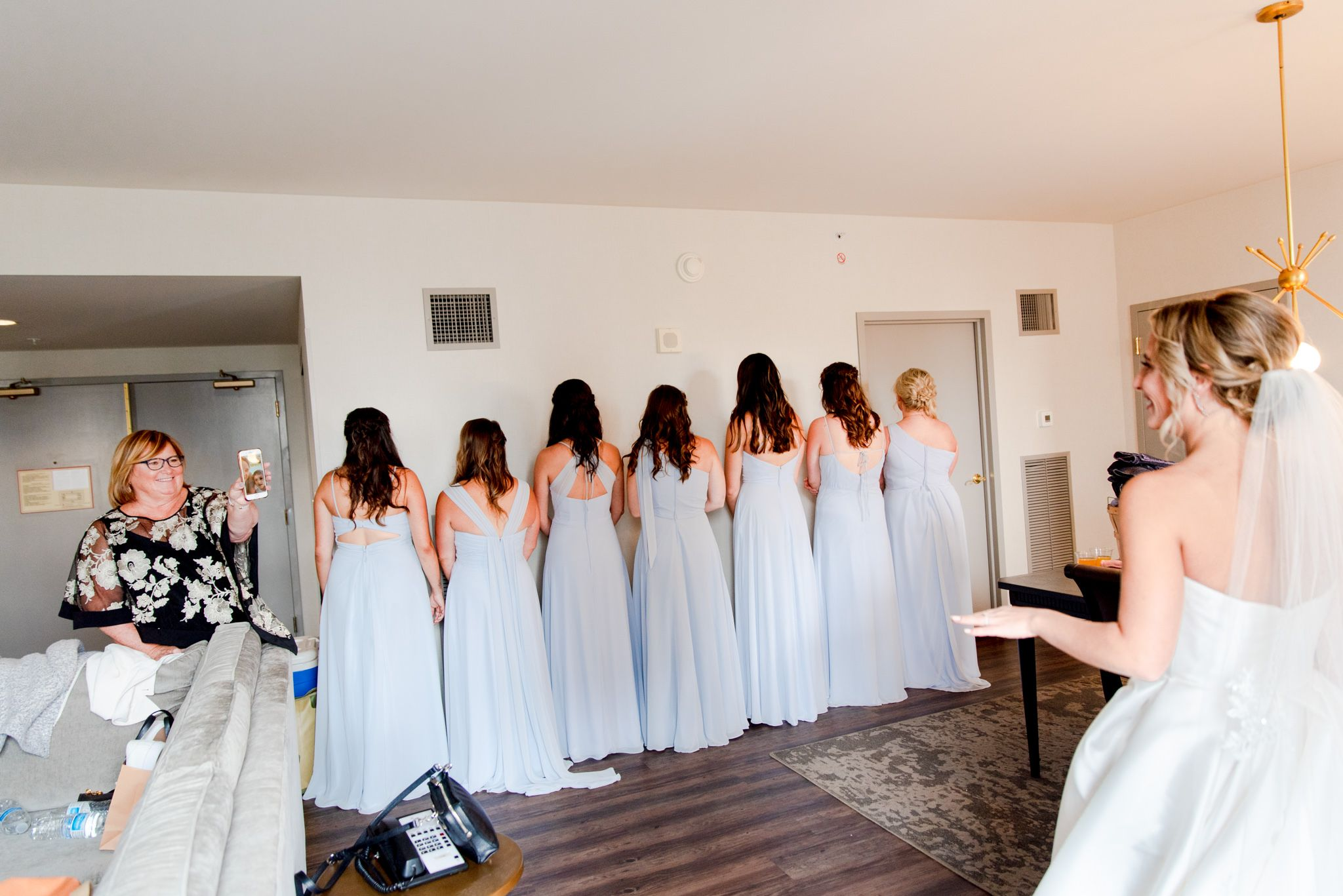 seven bridesmaids in ice blue dresses face the wall and wait to see the bride while mom facetimes family members