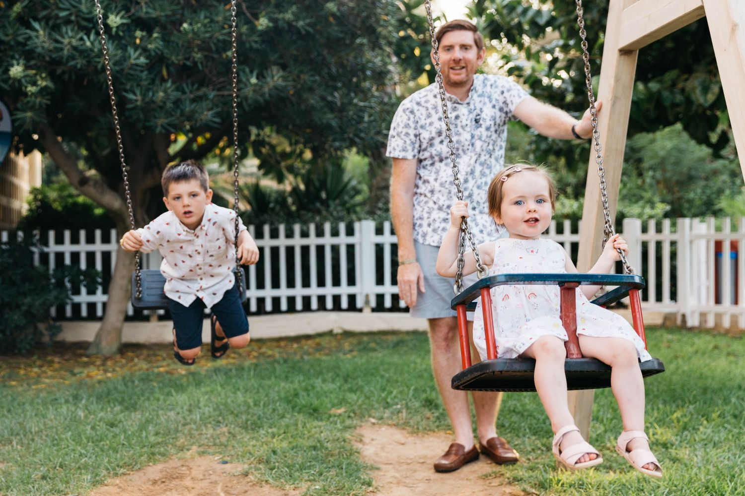 dad with two small kids on swings at playground