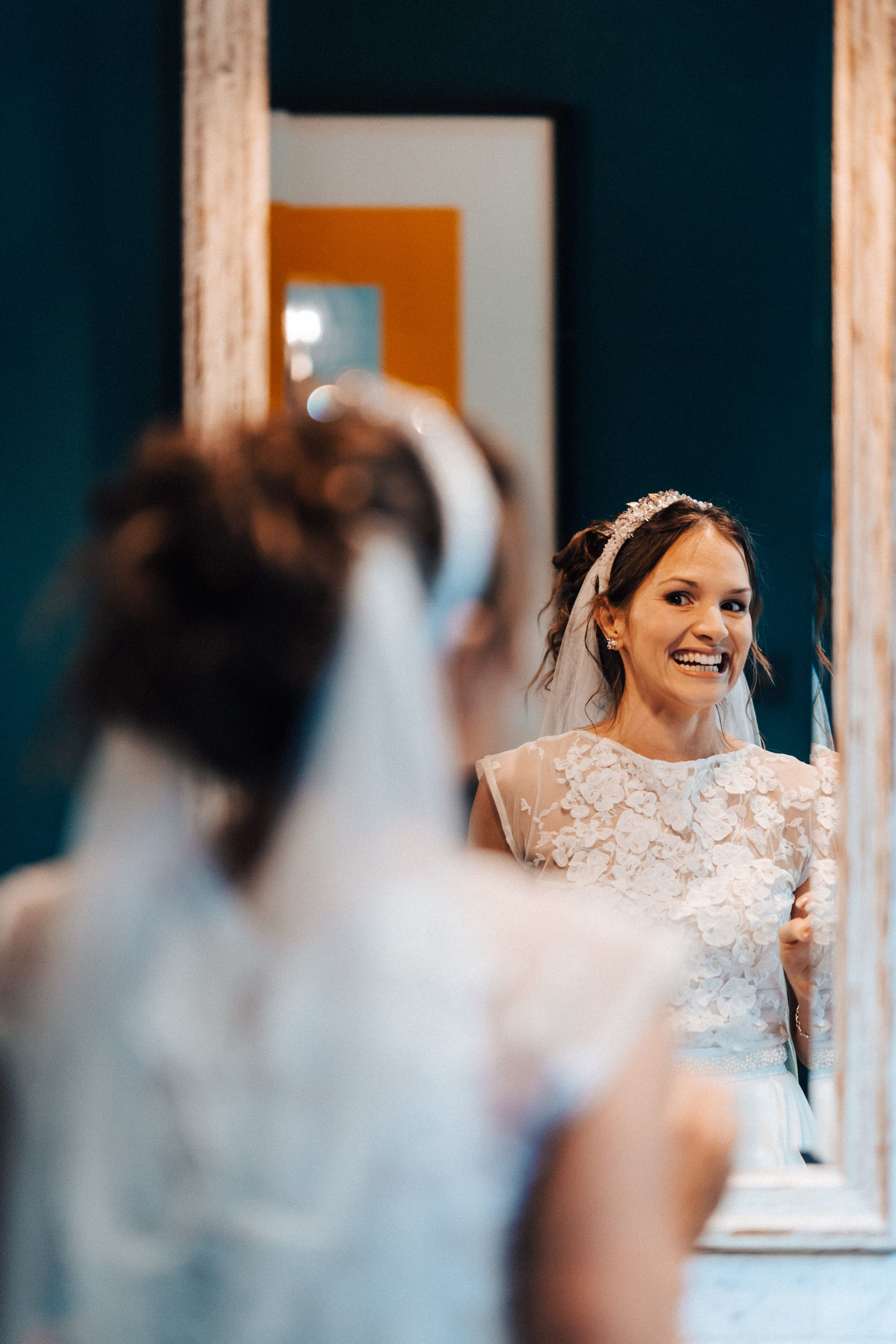 Candid reportage photograph of bride looking in the mirror at 131 Cheltenham bridal prep