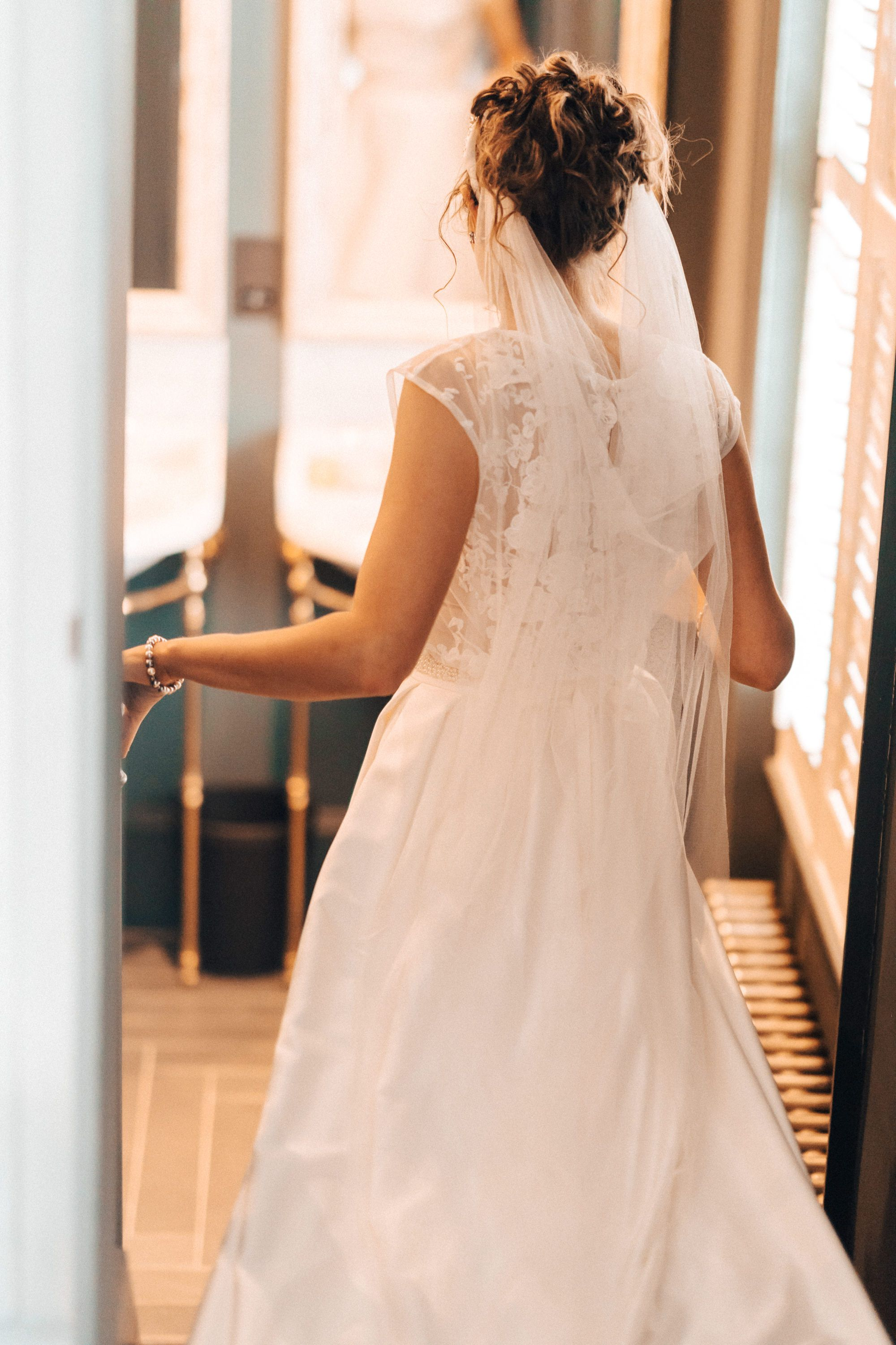Photograph of the bride dress from behind in bedroom