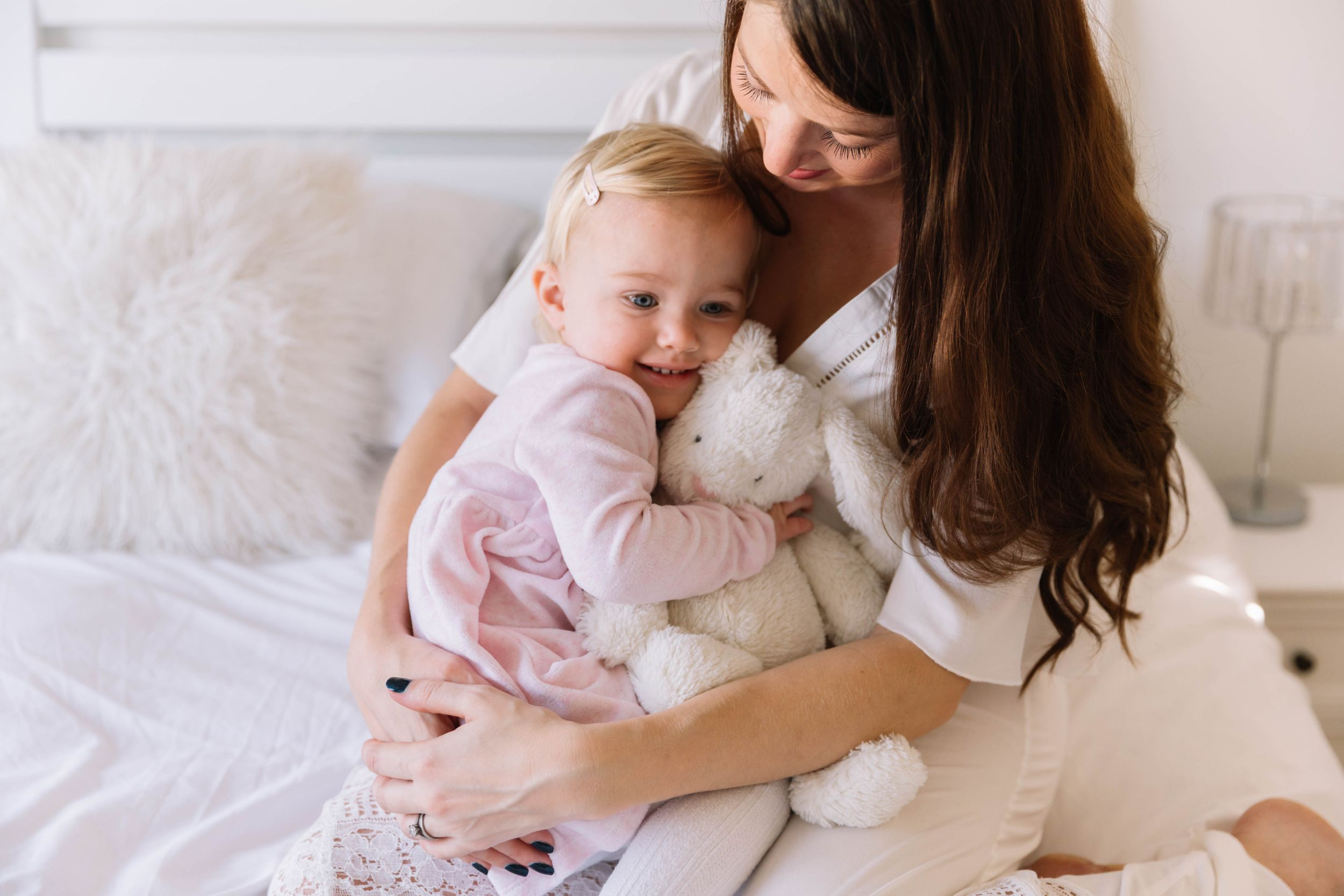pregnant mum in white dress and toddler daughter in pink dress cuddling on bed