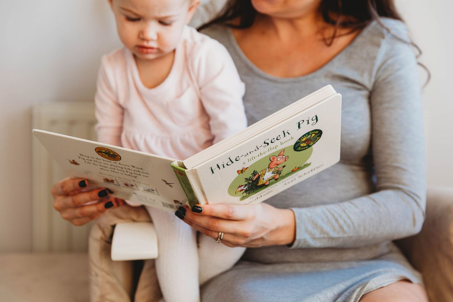 woman reading picture book to little girl
