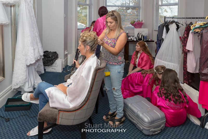 bride sitting in a chair having her hair done as the bridal prep chaos continues around her