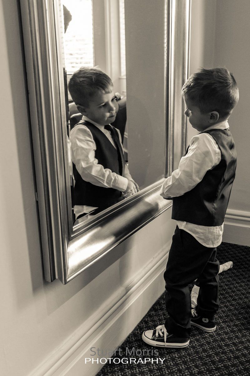 young pageboy stands looking at himself in a large full length mirror