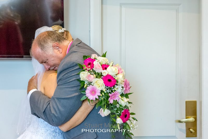 bride gets a big hug from her dad after he sees her for the first time in her dress