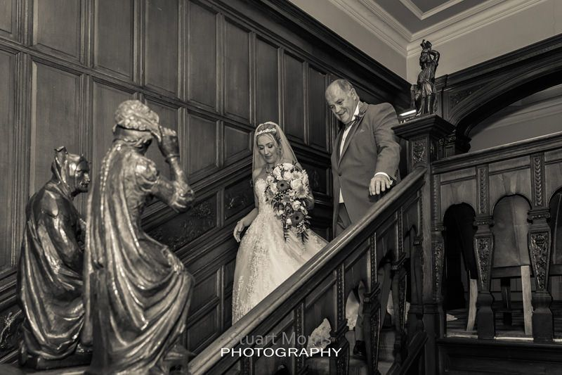 bride and her father walk down the wooden staircase at thornton hall