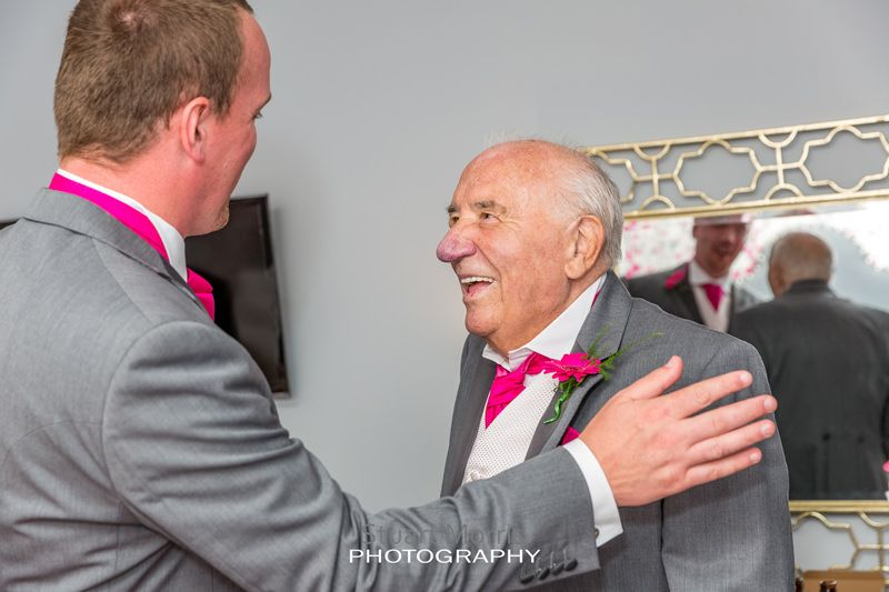 brides smiling grandad gets a pat on the shoulder from one of the groomsmen