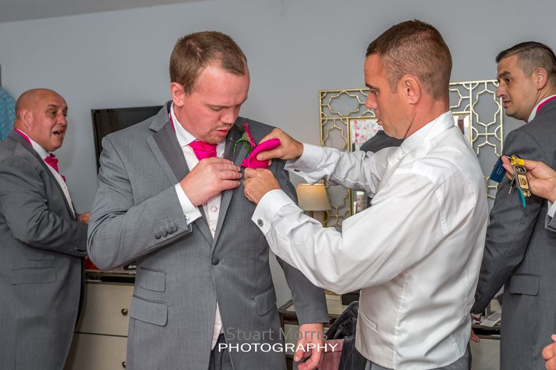 the groom helps one of the groomsmen with his buttonhole