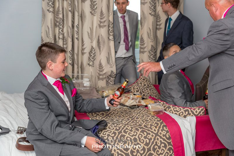 young groomsman eyes up a bottle of beer during the prep as a groomsman tries to take it from him