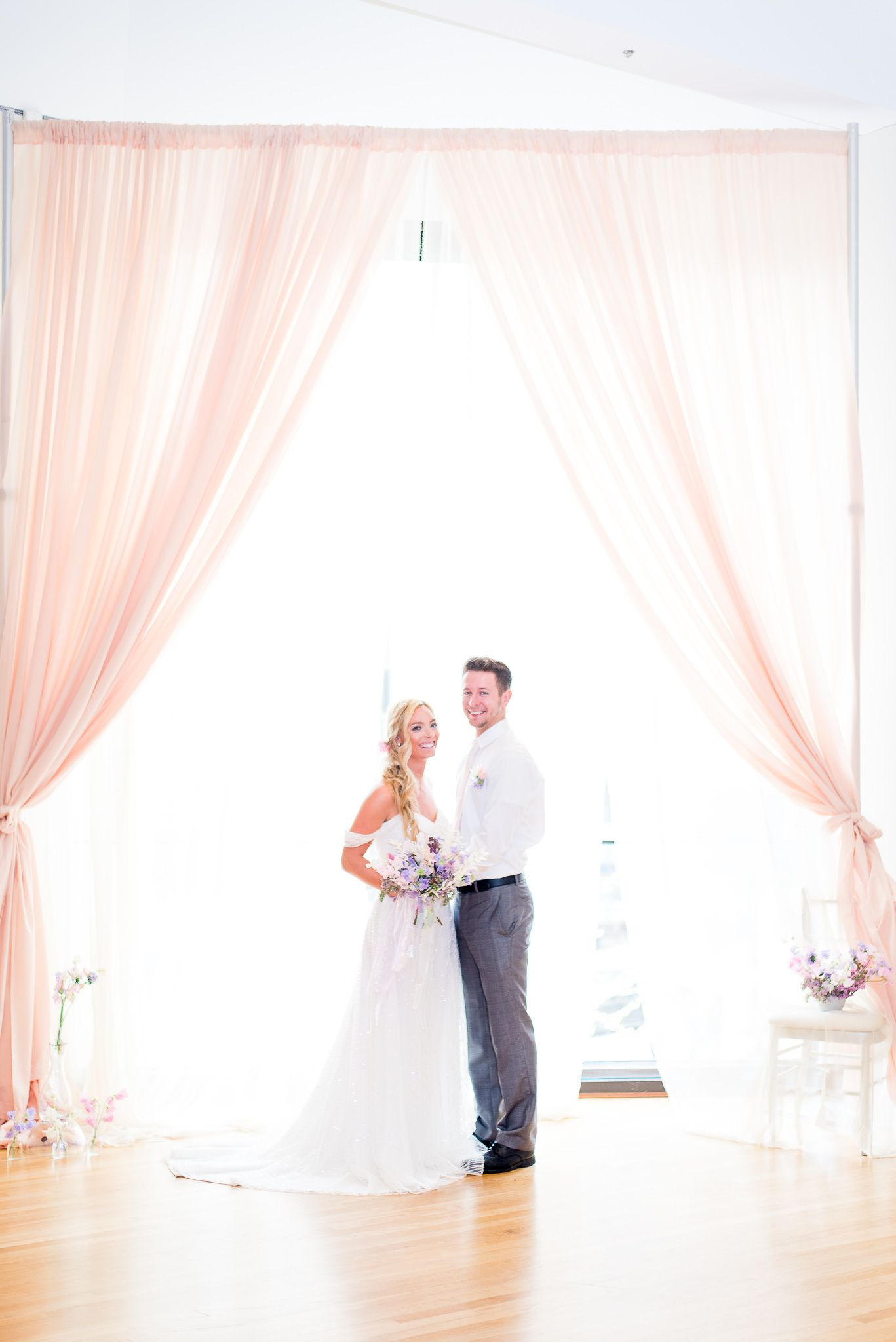 bride and groom smiling in front of pale pink curtains and window at The Center Cincinnati