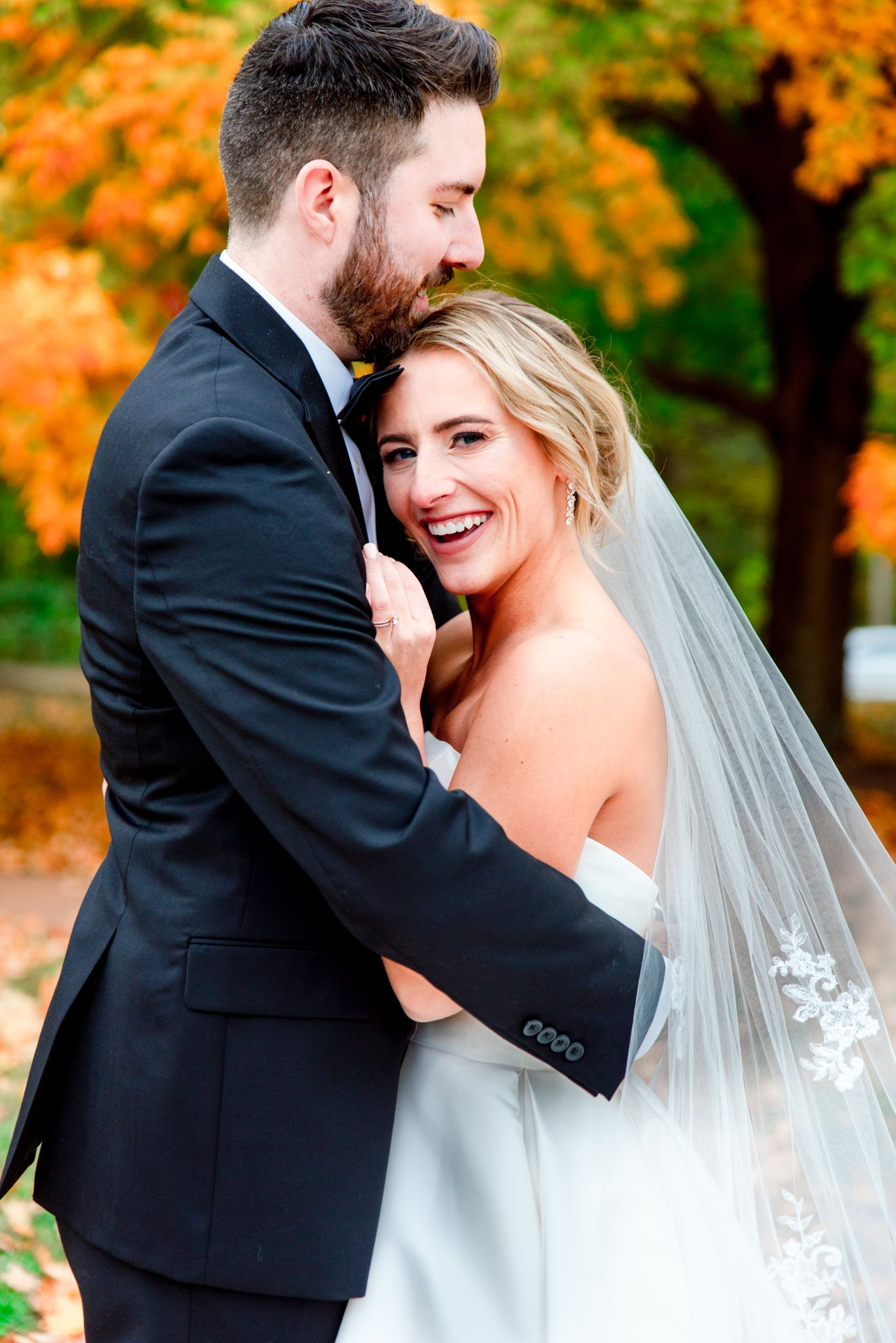 bride with lace veil leaning on grooms chest, who is hugging her in front of orange tree
