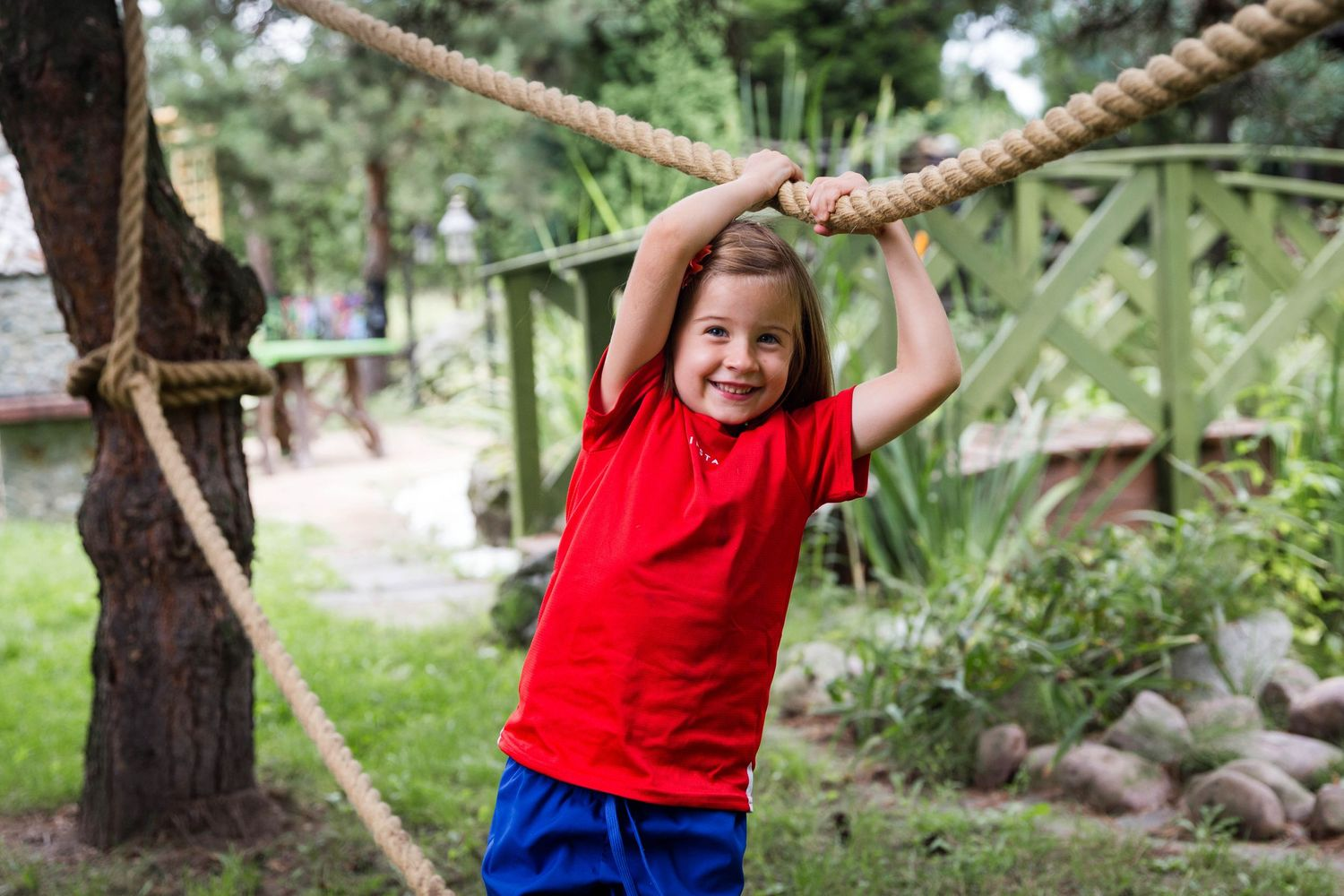 girl in red t-shirt smiling holding rope