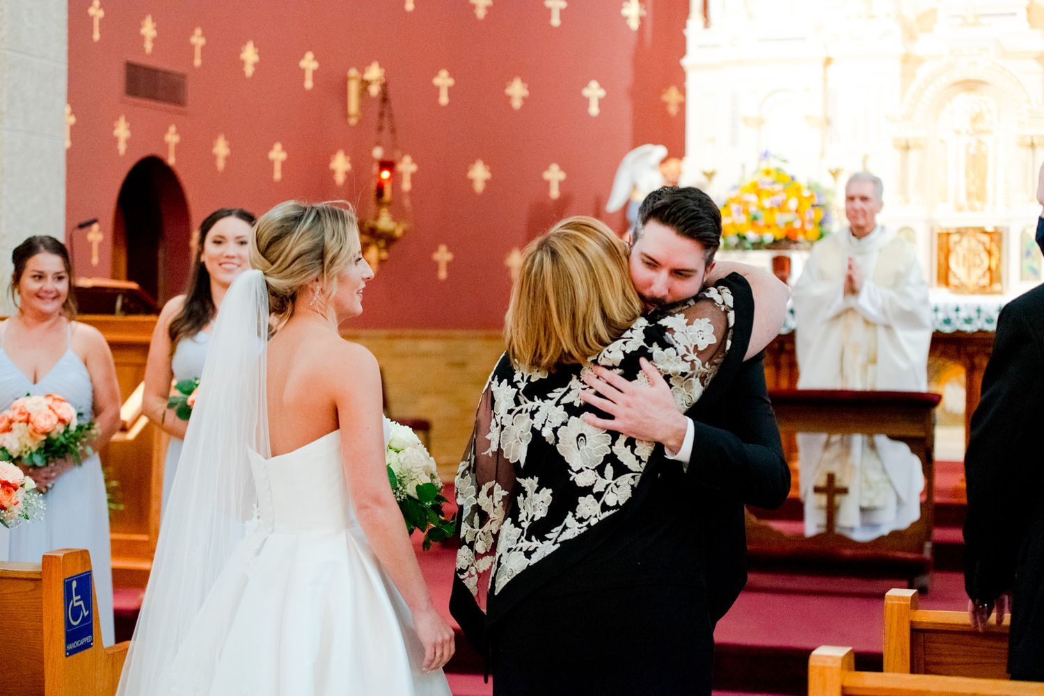 groom and mother of the bride hugging at the church altar before wedding ceremony
